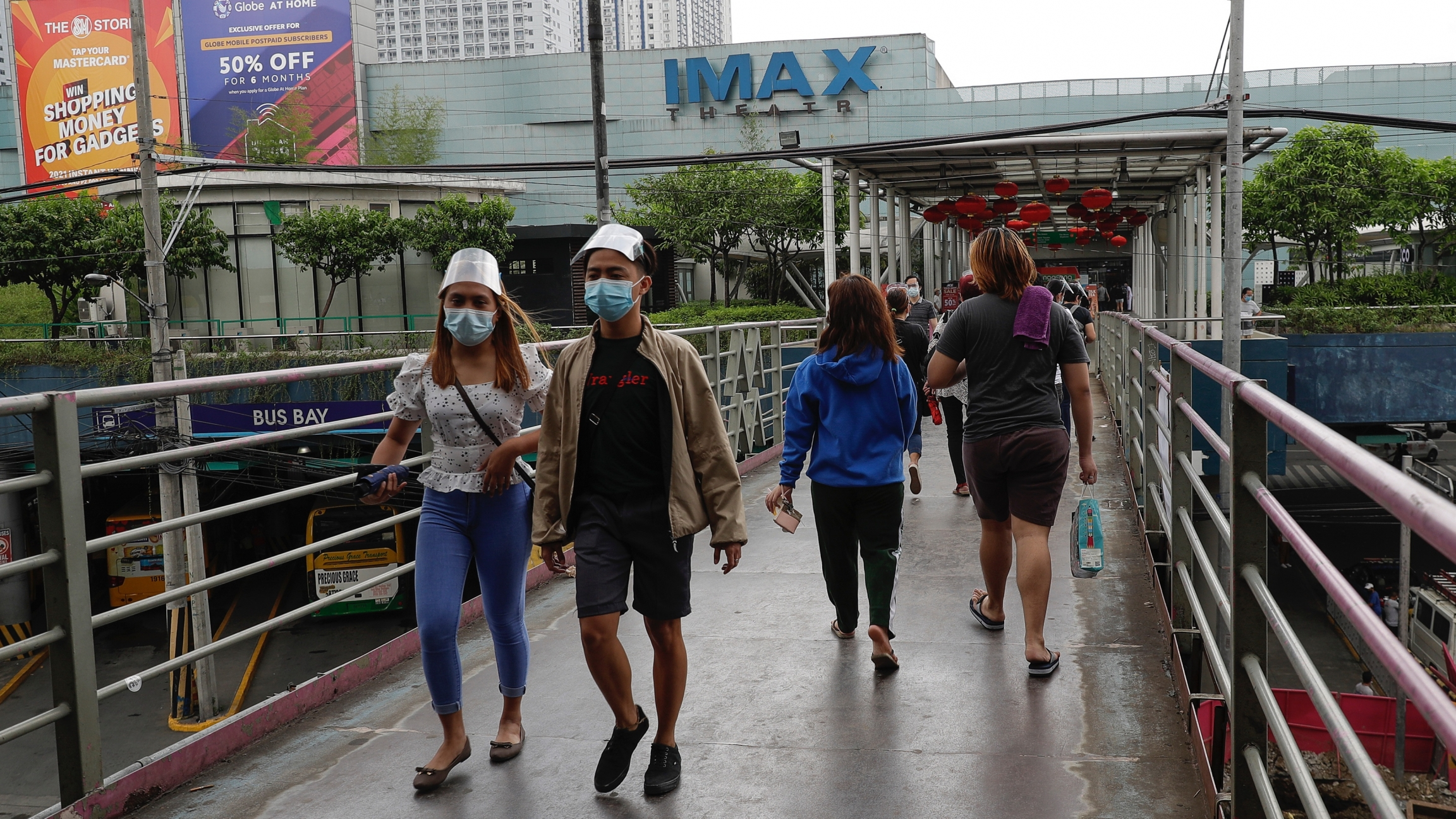People walk wearing face masks and shields over a bridge near a mall