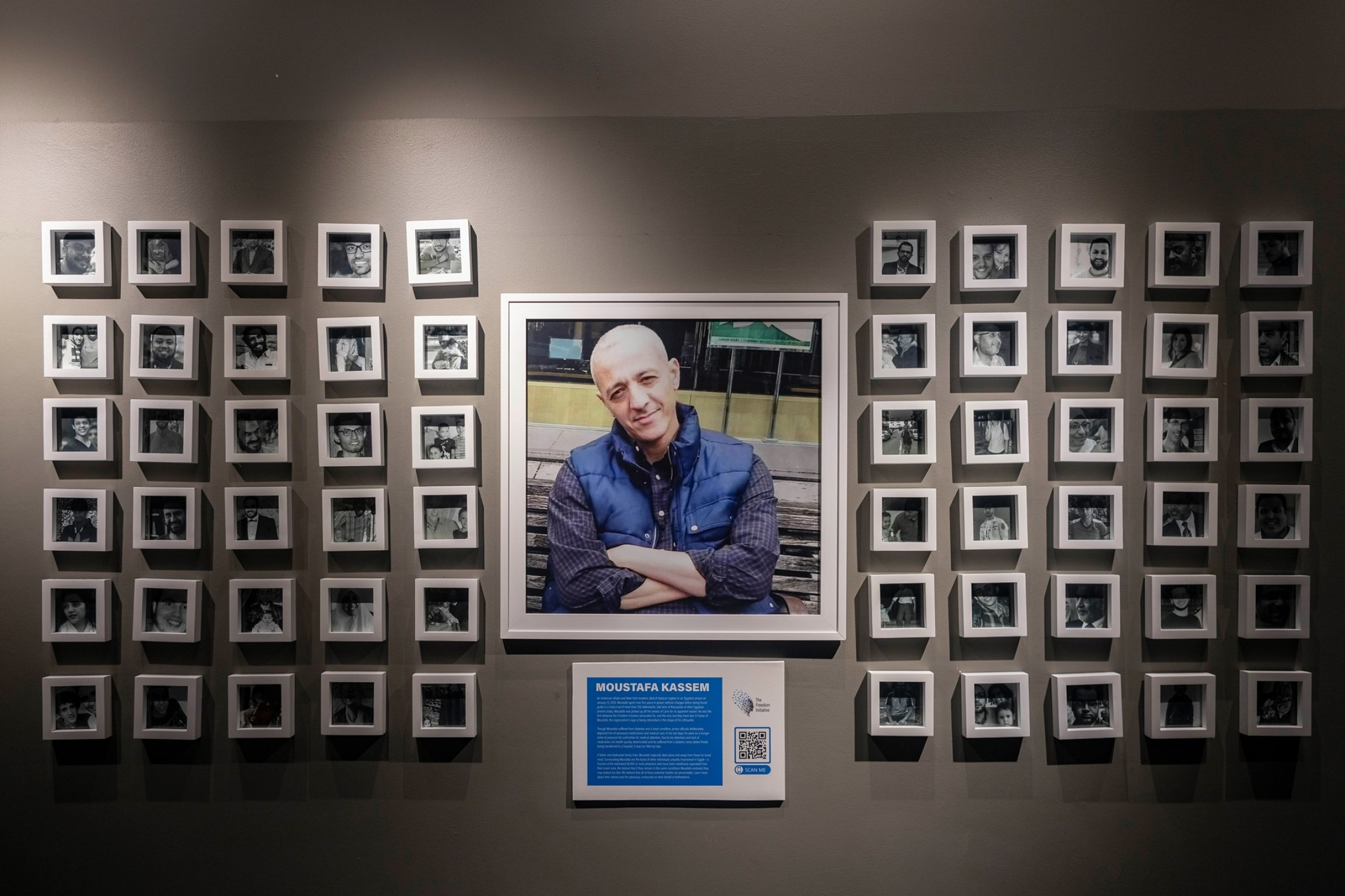 A memorial shows a photo of a man surrounded by several other frames in a gallery.