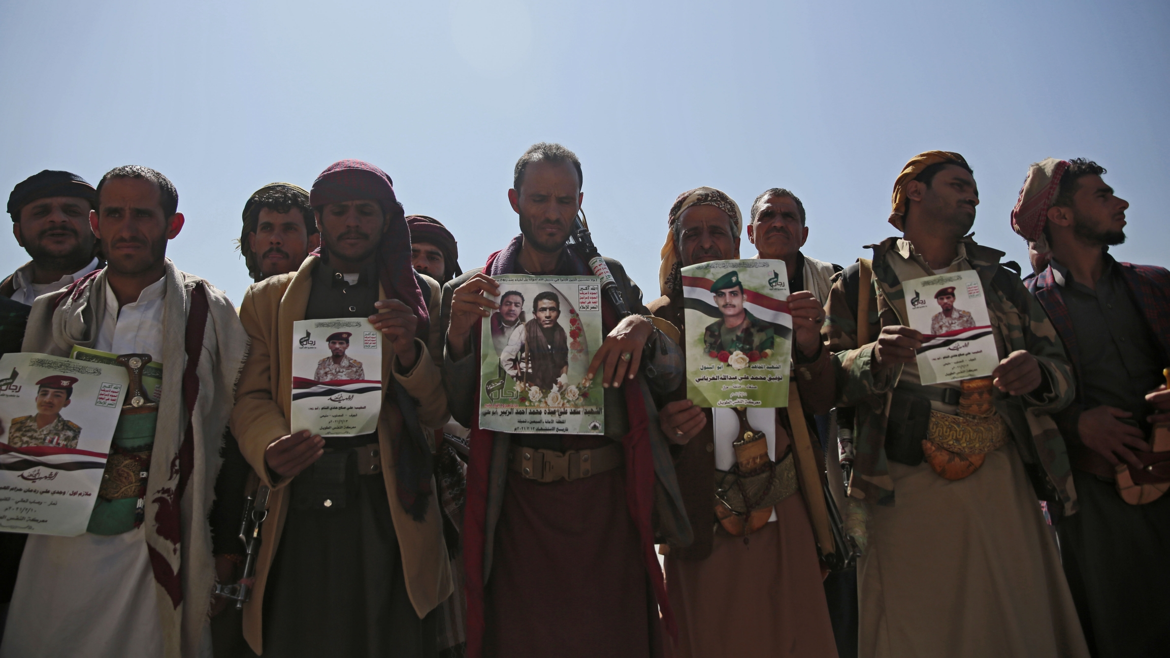 Houthi fighters hold images of relatives killed in violent conflict