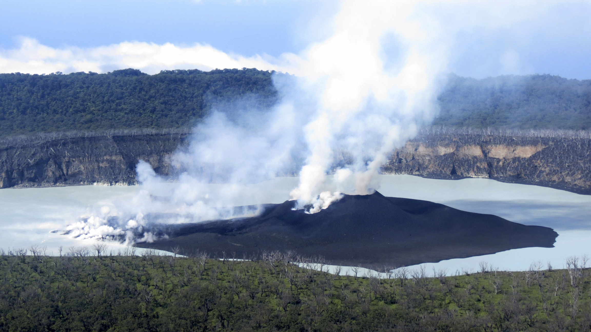 A dark volcano with smoke rising out of it surrounded by a body of water.