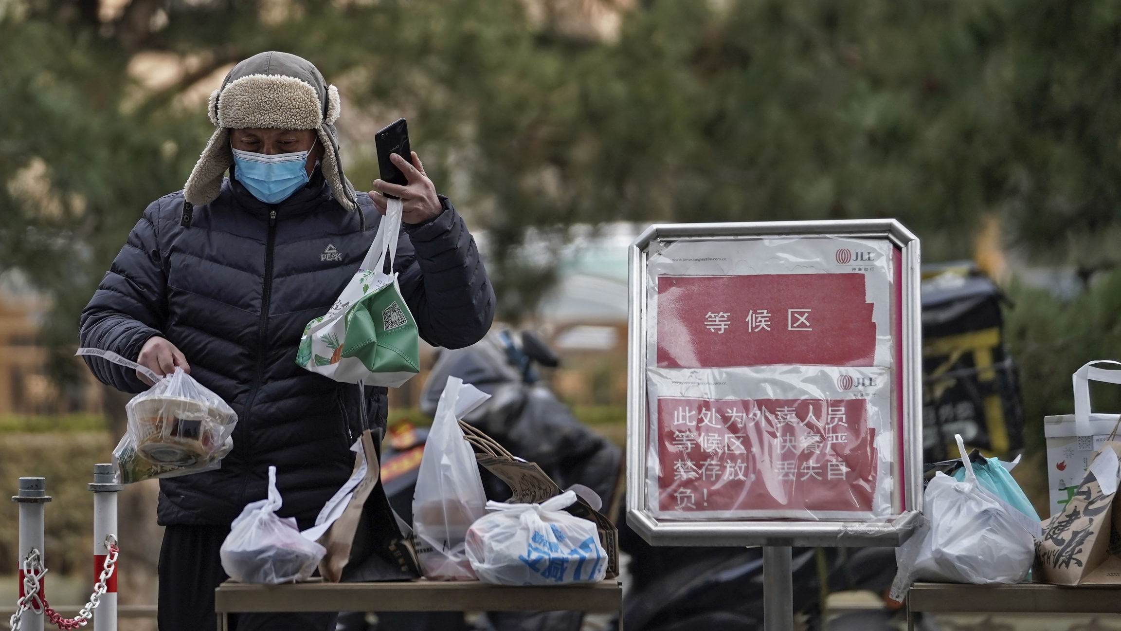 A delivery driver wearing a mask organizes food packages outside.