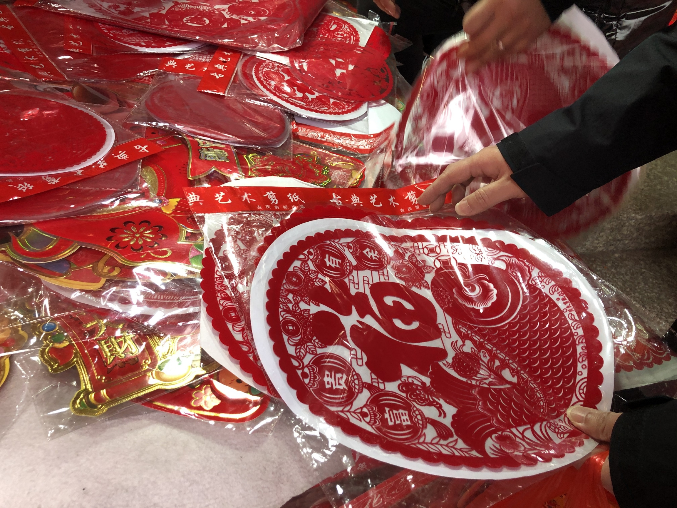 The Chinese government hasn't actually forbidden holiday travel this year, but they're strongly discouraging it. So, many people are staying put and finding other ways to celebrate the Chinese New Year — like with red decorations and the like sold in Shan