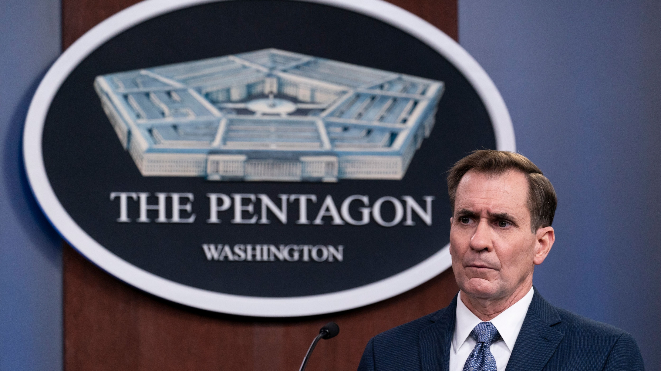 Pentagon spokesman John Kirby is shown wearing a dark blue suit and standing behind a microphone with the logo for the Pentagon behind him.