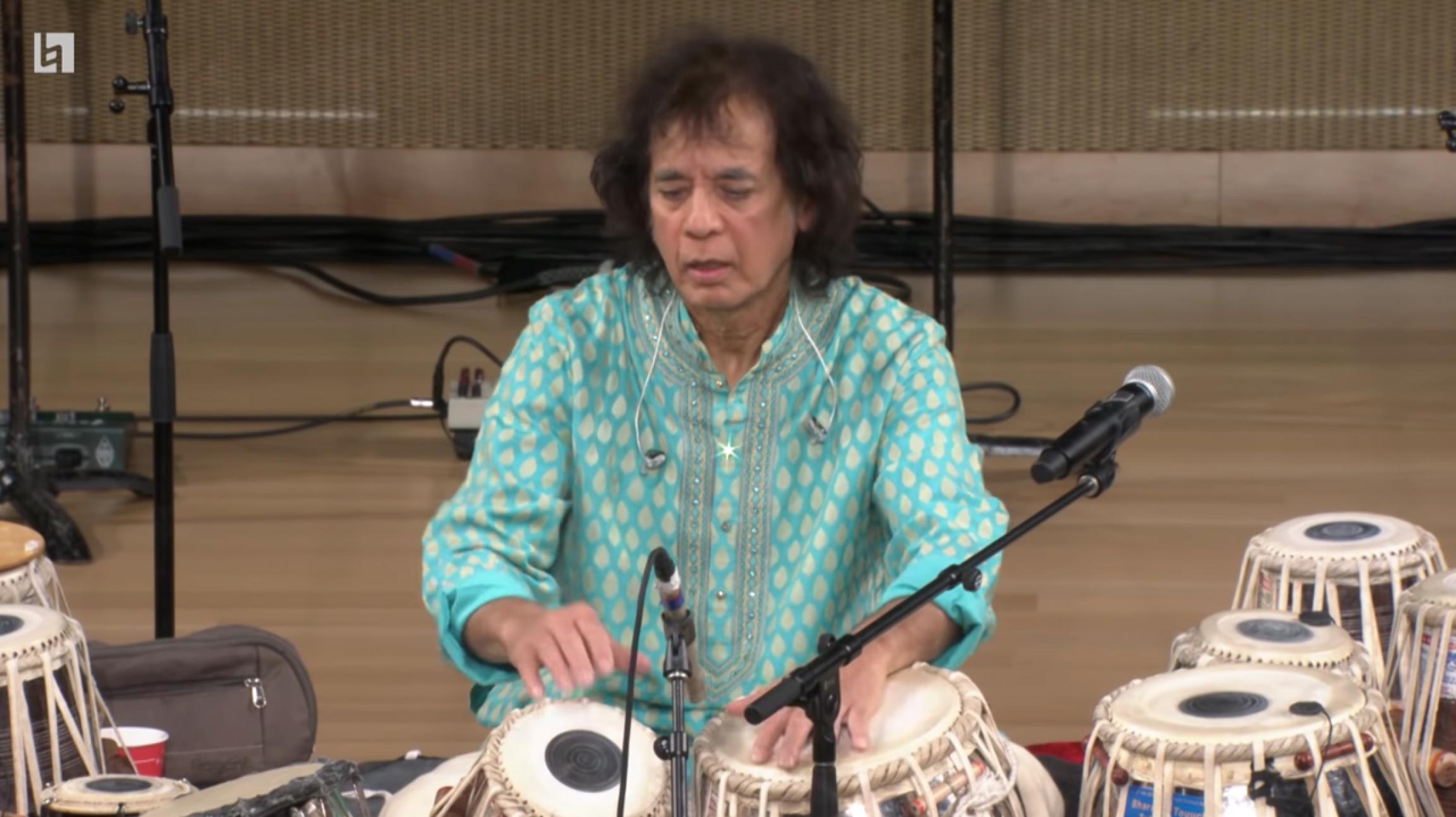 A man plays tabla while wearing a light blue shirt.