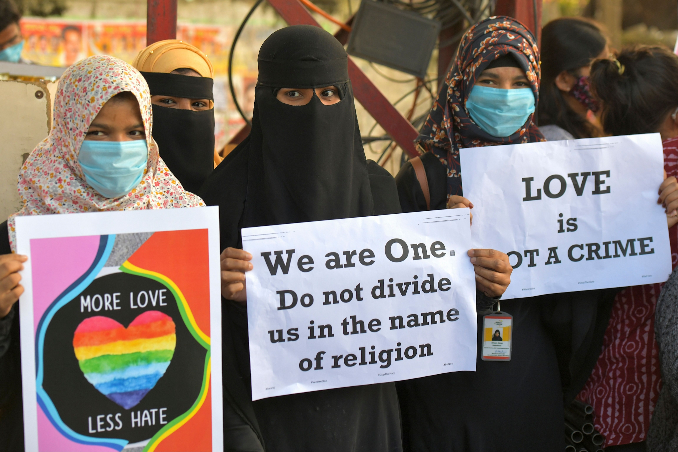 "Three women protestors hold up signs reading ""More Love, Less Hate""; ""We are One. Do not divide us in the name of religion""; and ""Love is not a crime."""