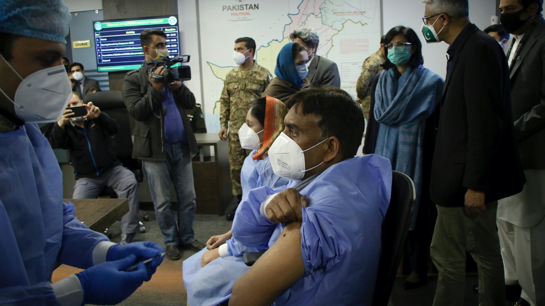A health worker administers the Chinese Sinopharm COVID-19 vaccine to his colleague while the prime minister's adviser on health issues Faisal Sultan, second right, and other officials watchduring a ceremony to start the vaccination campaign in Islamabad