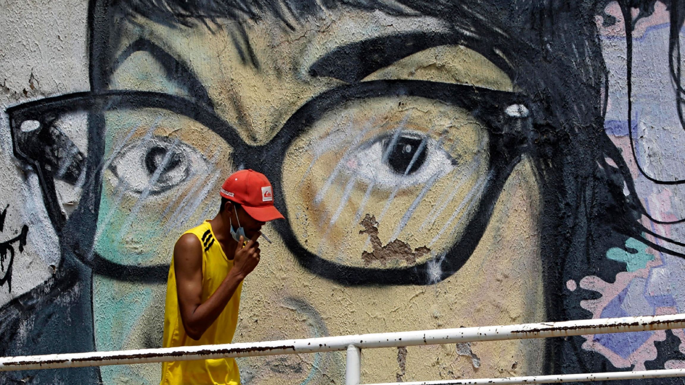 A man wearing a yellow sleave-less shirt and red hat is shown smoking a cigarette and walking past a large mural of someone wearing glasses.