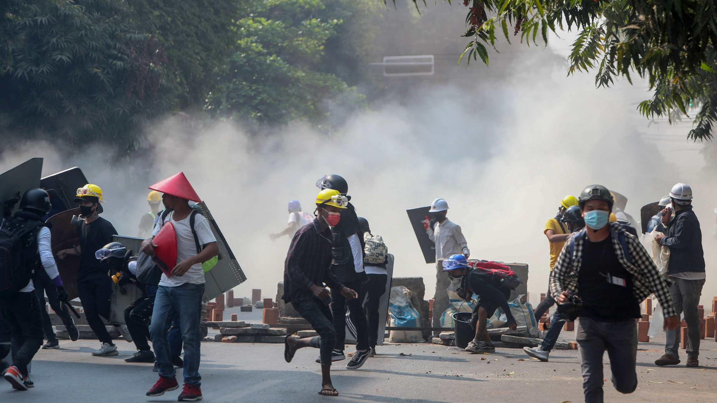 A large group of protesters are shown running from a cloud of tear gas in the foreground with several people wearing construction hard hats.