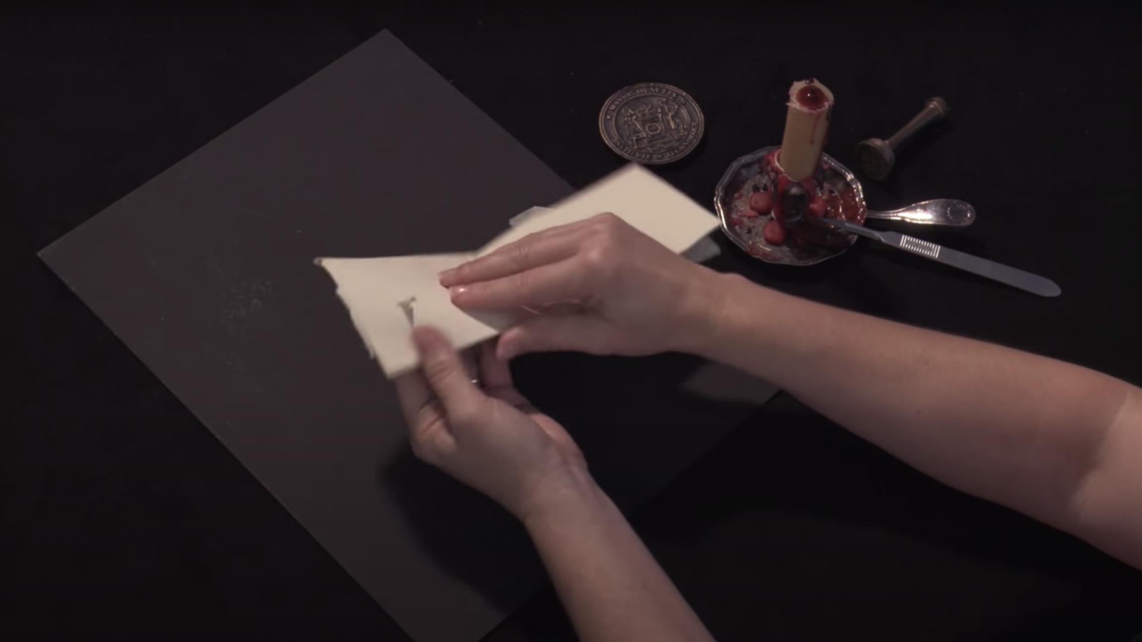 Hands fold a sheet of paper