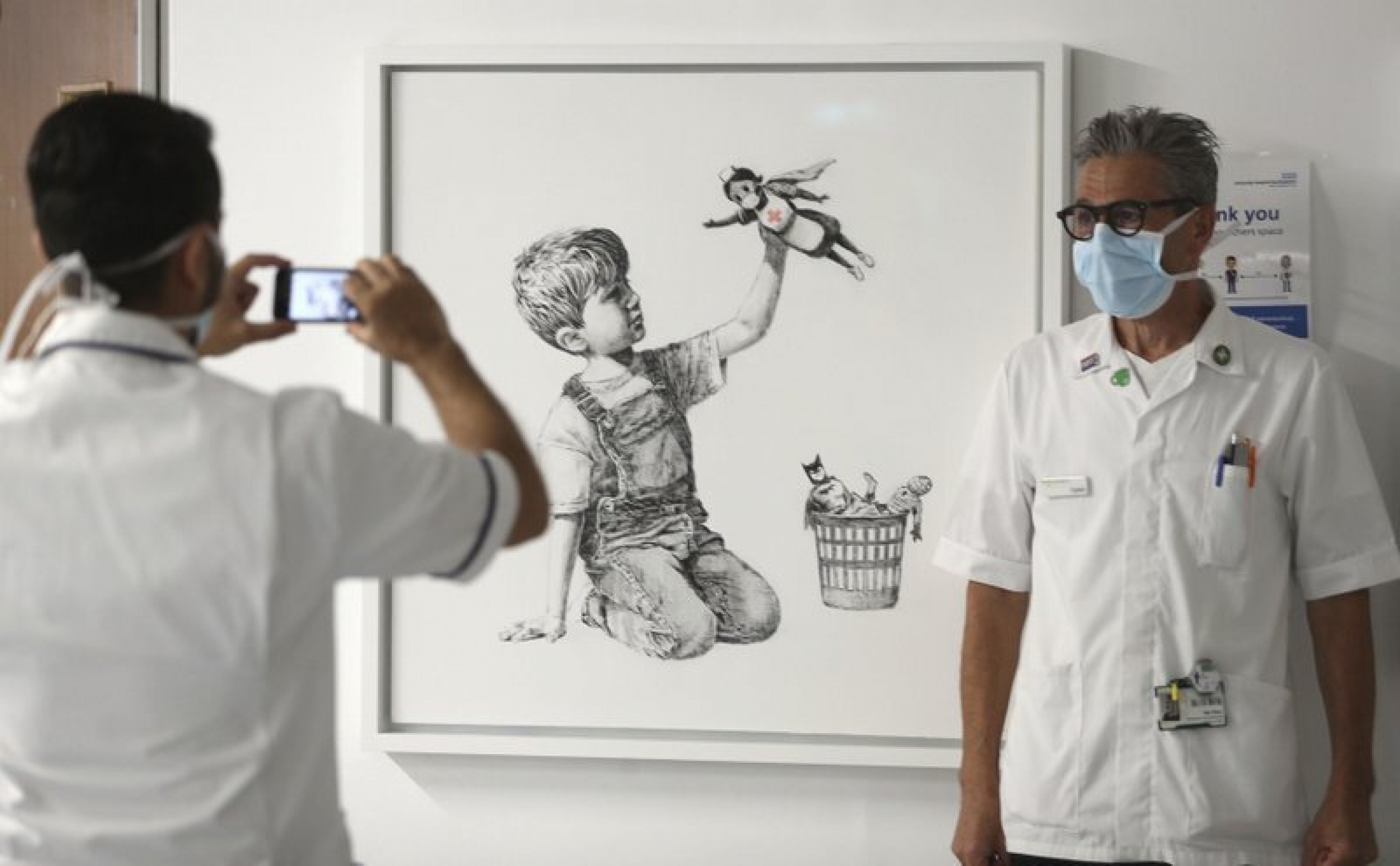 A member of a hospital staff is shown standing next to a Banksy artwork while getting their photograph taken.