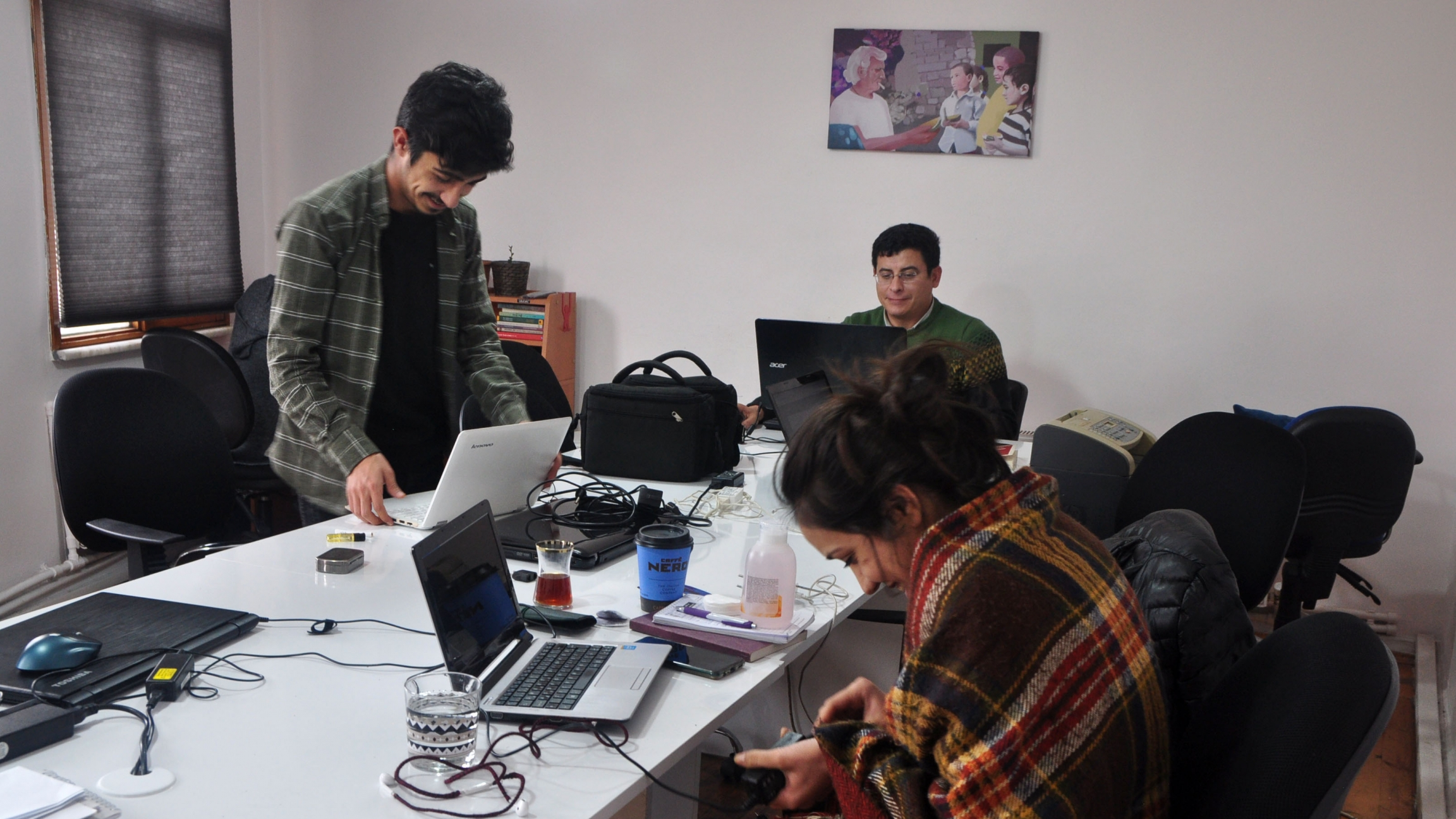 A team of journalists gather around a table with laptops