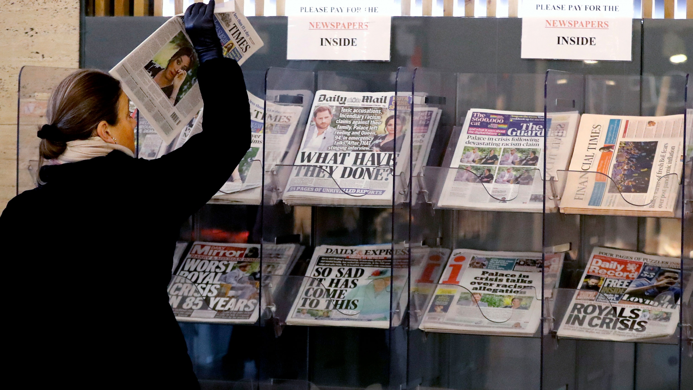 A woman is shown wearing a dark coat and pulling a newspaper out of a stand in a row of several other newspapers.