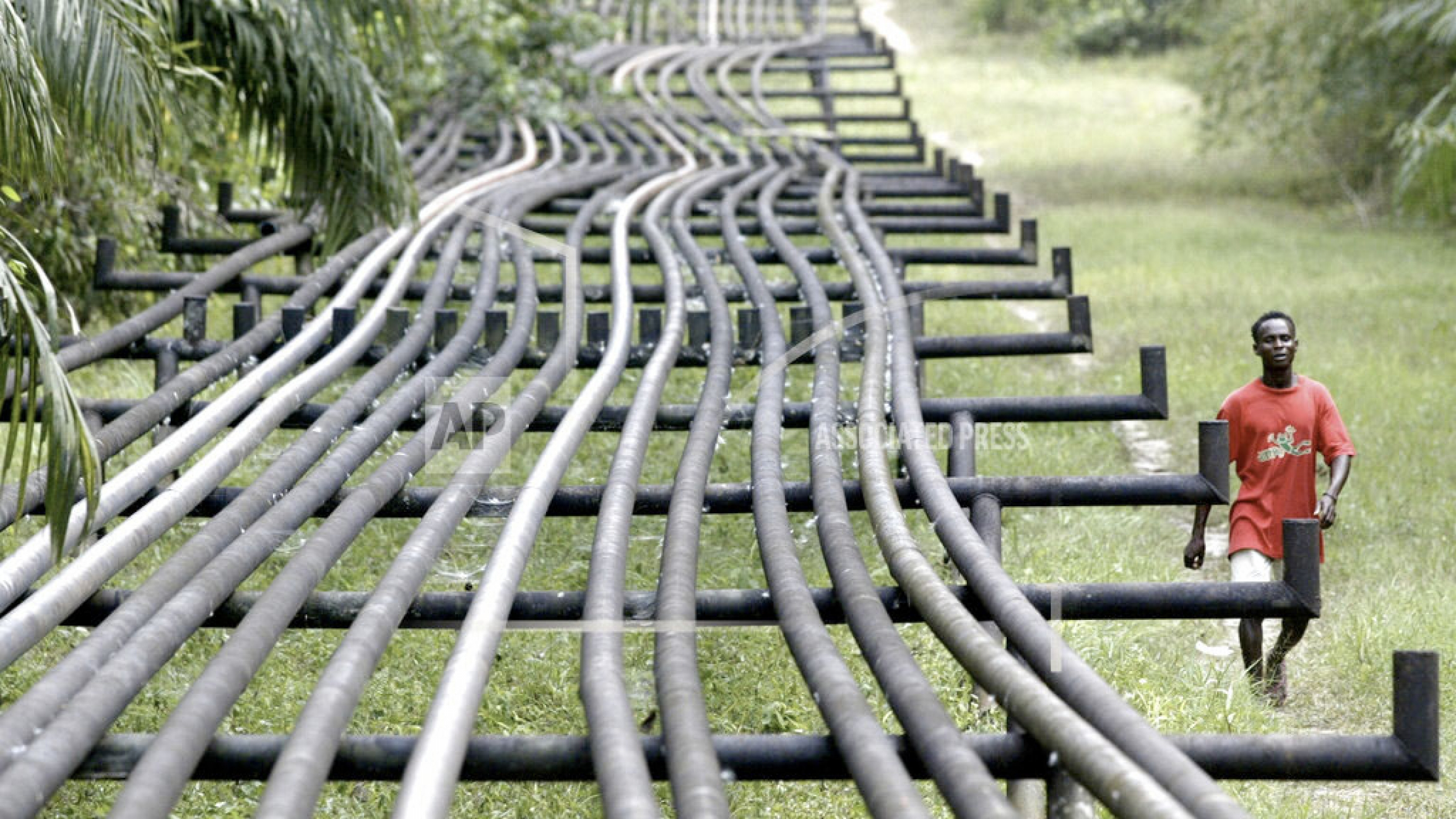 An unidentified man walks along oil pipelines belonging to Agip Oil company in Obrikom, Nigeria, Monday, March 6, 2006.