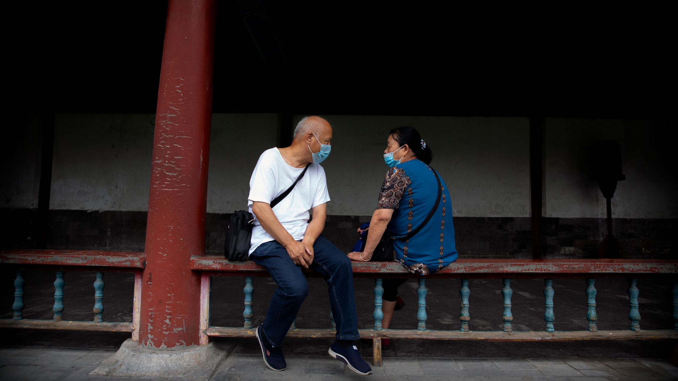 A man and woman are shown sitting on either side of a wooden railing and facing each other while wearing protective masks.