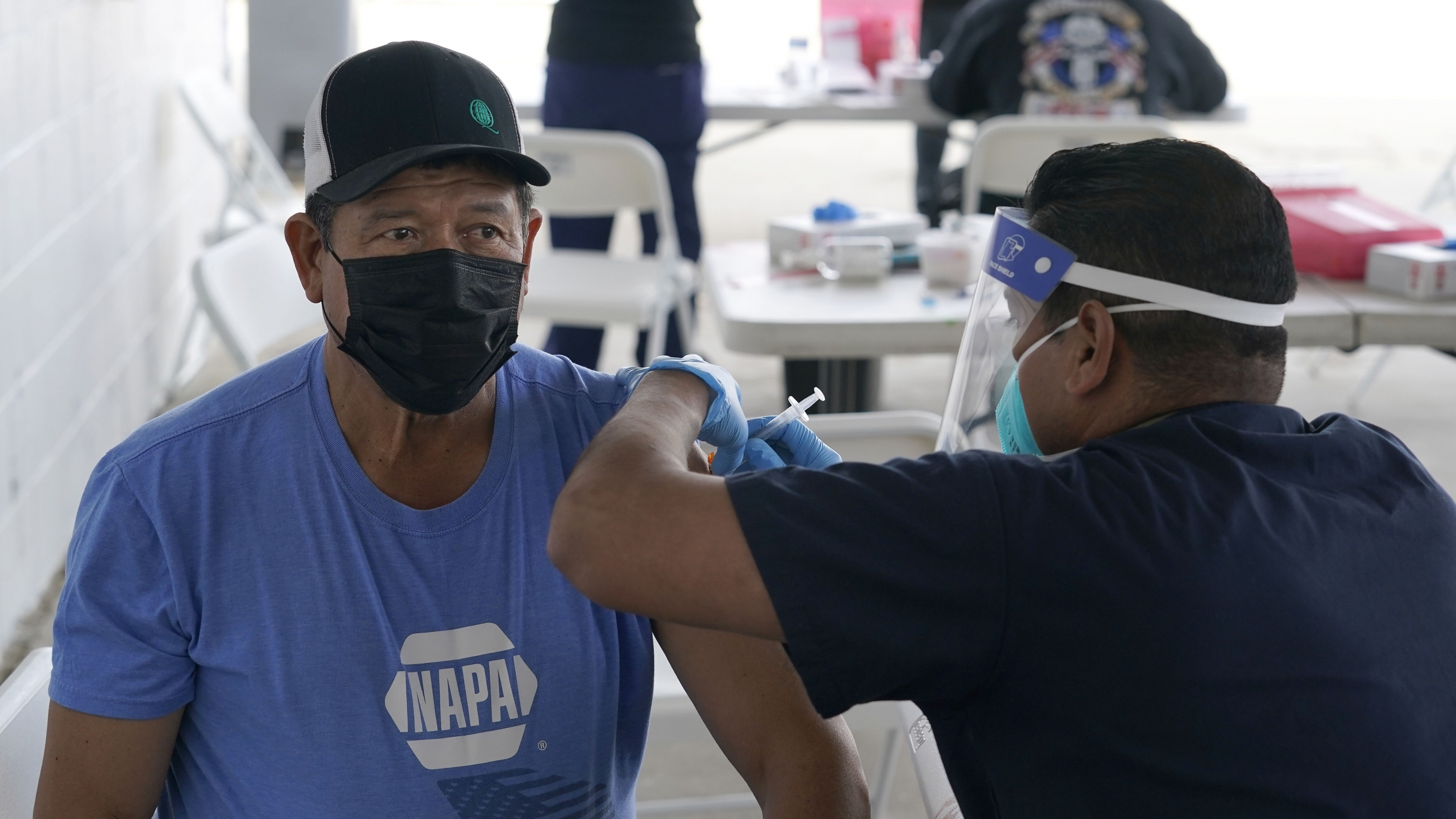 A man wearing a blue shirt and black cap gets a vaccine shot by a health care worker.