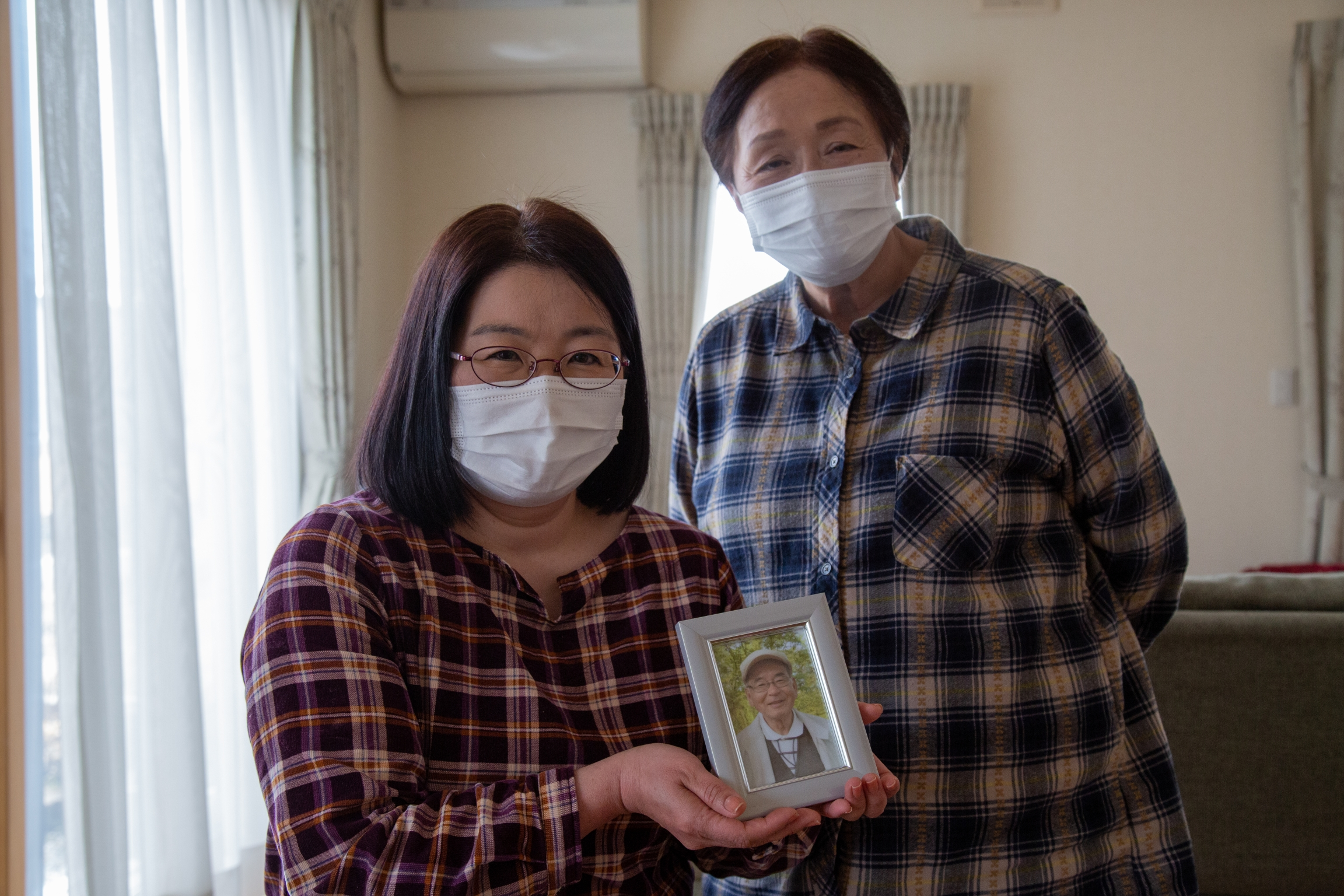 Two women are shown next two each other, both wearing medical face masks and one holding a small framed photograph.