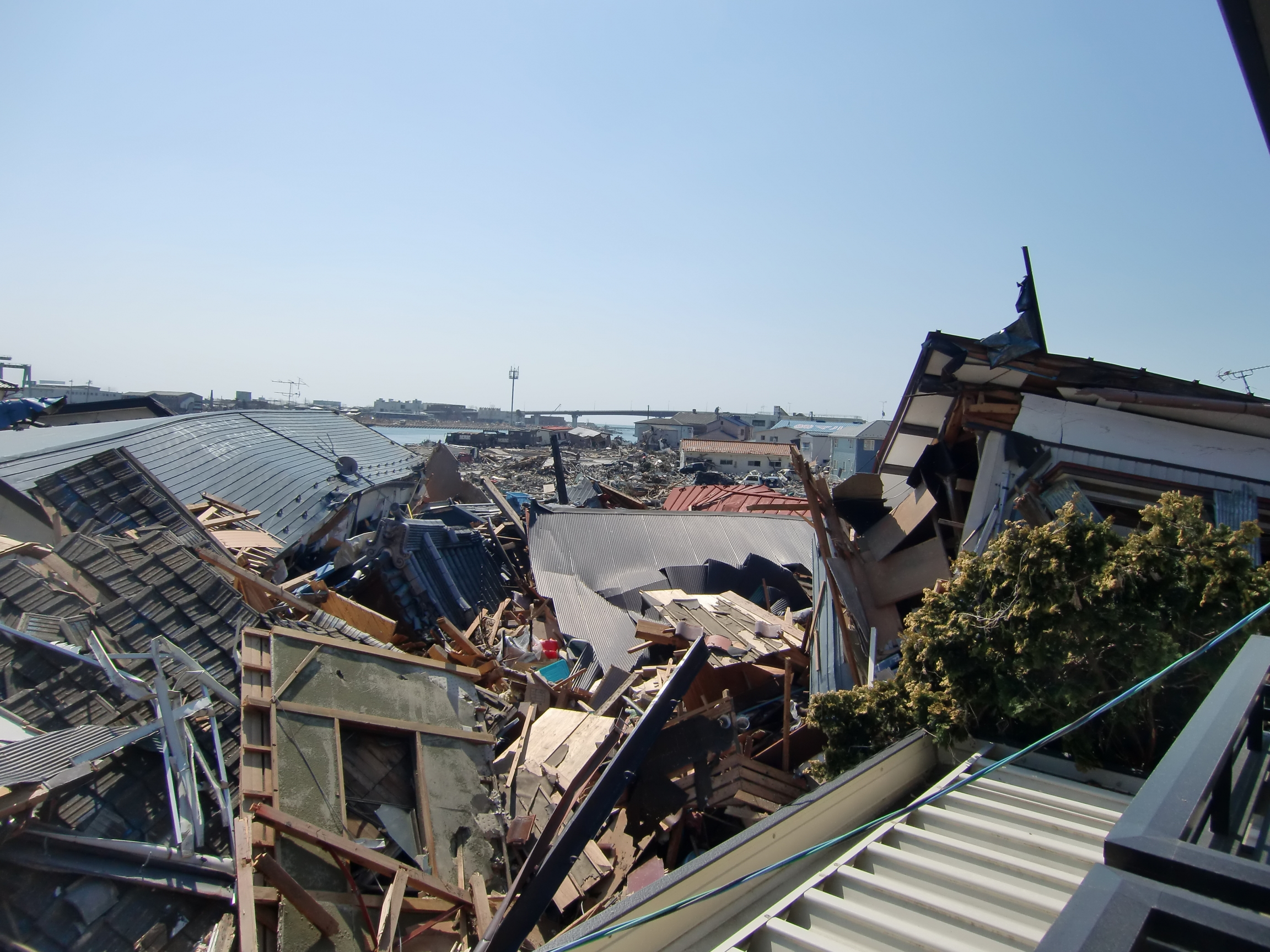 Houses are shown destroyed and collapsed on each other.