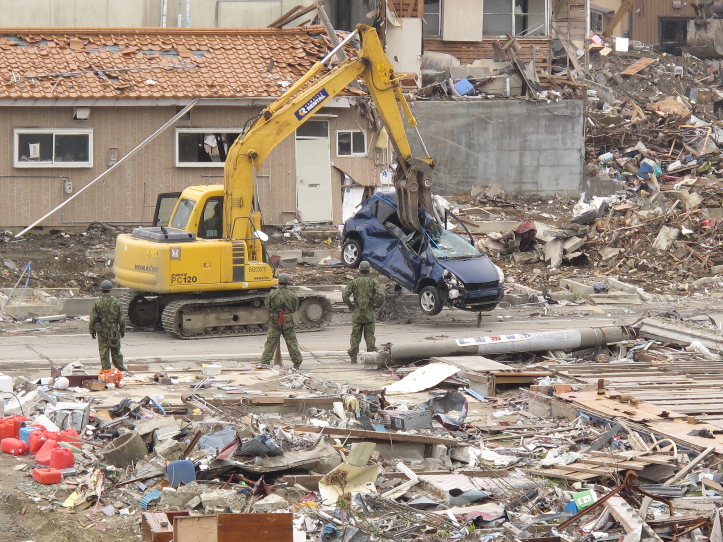 A yellow crane with a long arm is shown lifting up a destroyed blue car with damaged buildings all over.