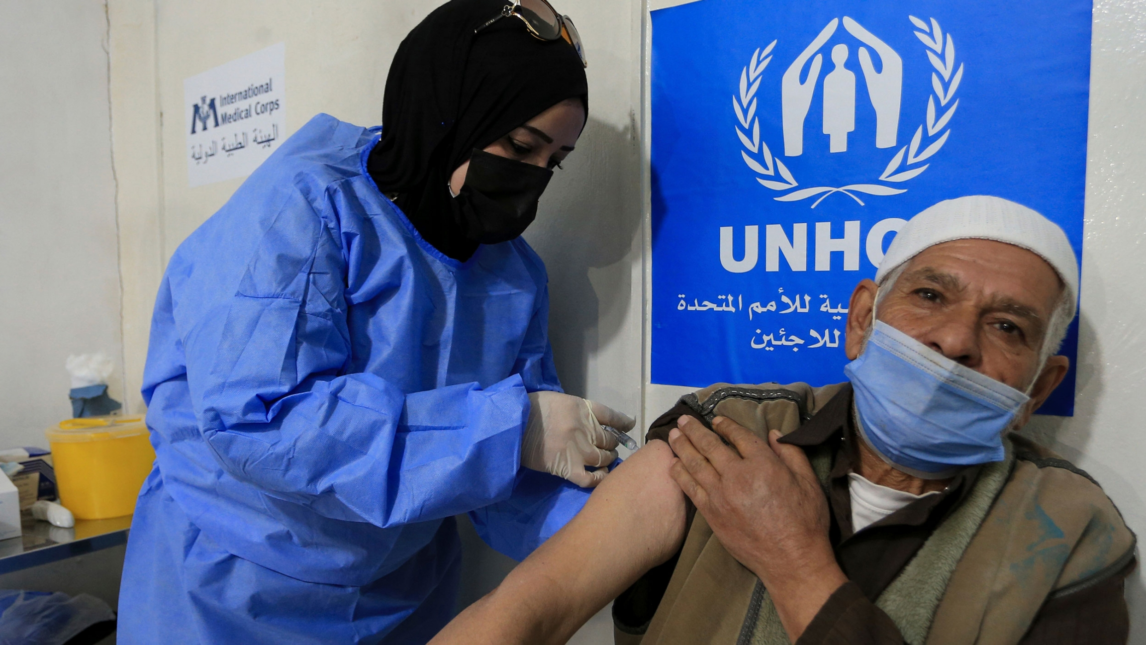 A man is shown holding up his sleeve as a nurse, standing next to him, injects him with a vaccine.