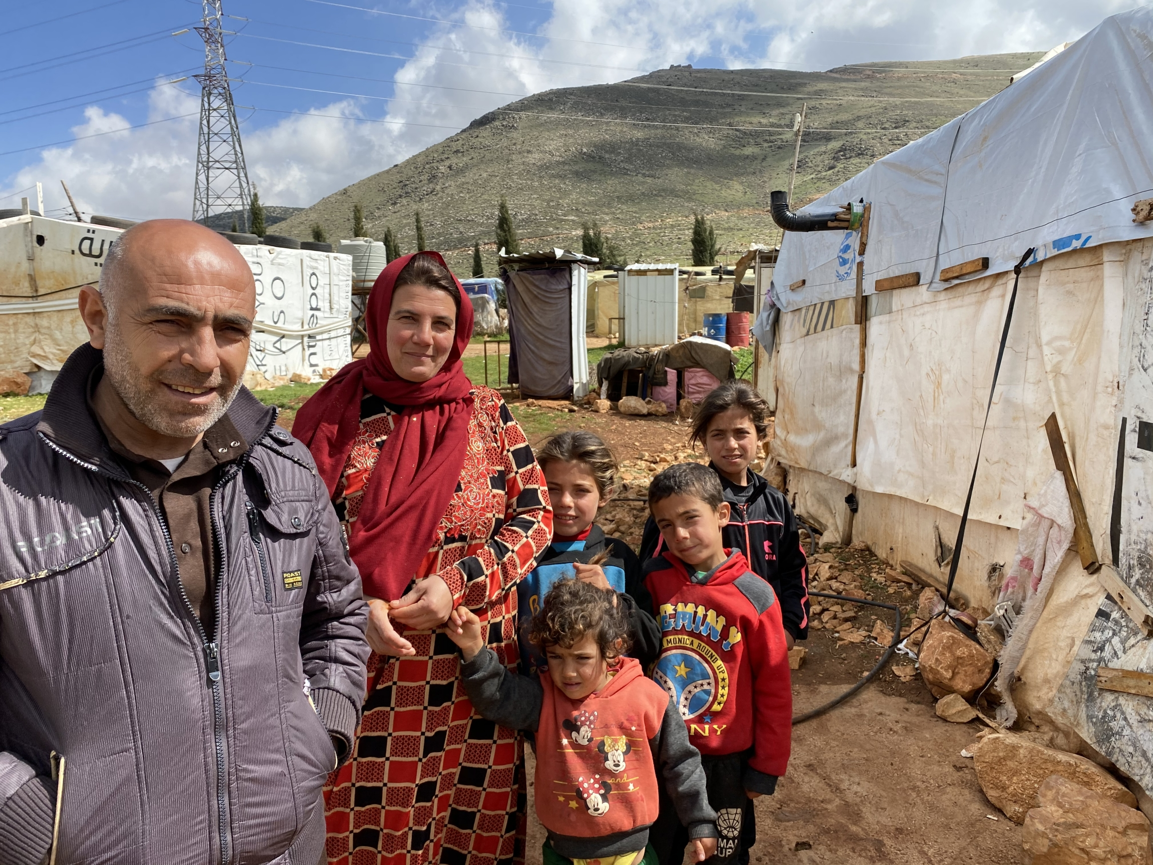 Ali Hamoud stands in front of his tent with his family. The mountains behind mark the Syrian border.