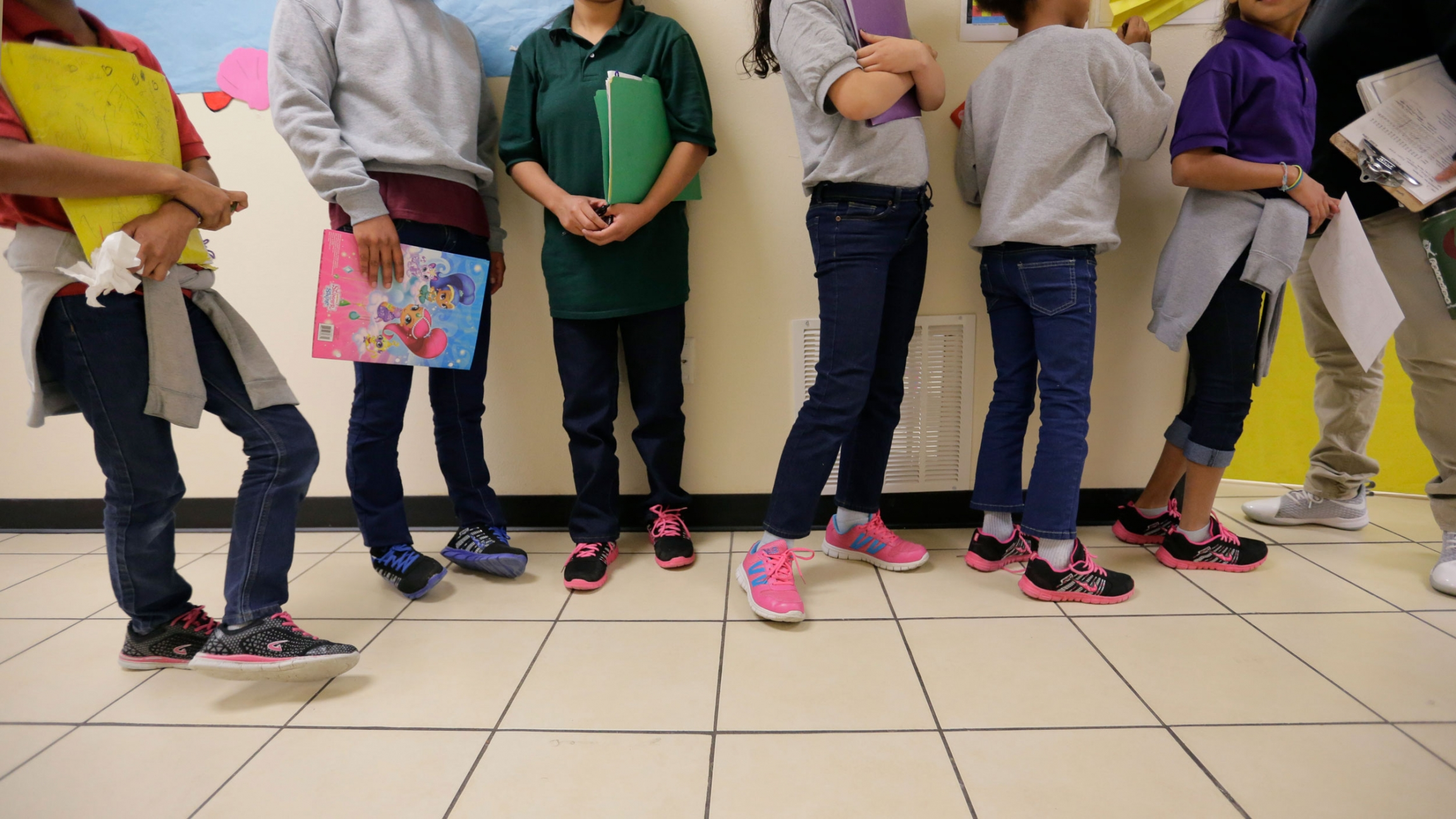 Several young people are show from their neck down and wearing sweatshirts and jeans and many with pink tennis shoes.