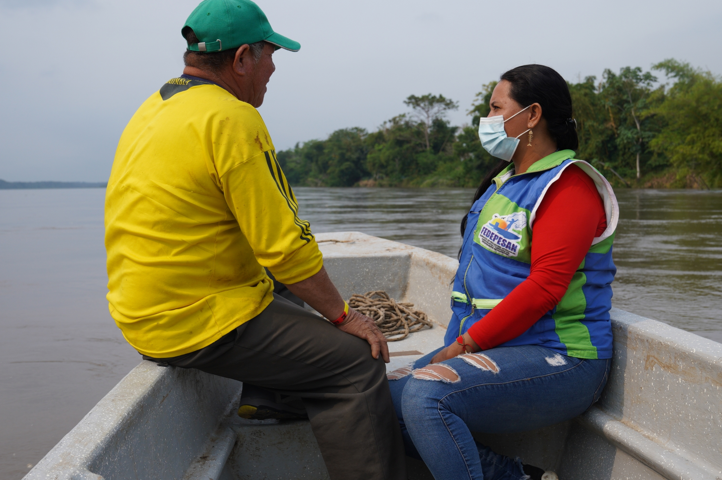 A man wearing a yellow shirt and green cap and a woman wearing a blue vest with a mask ride a boat on a river.