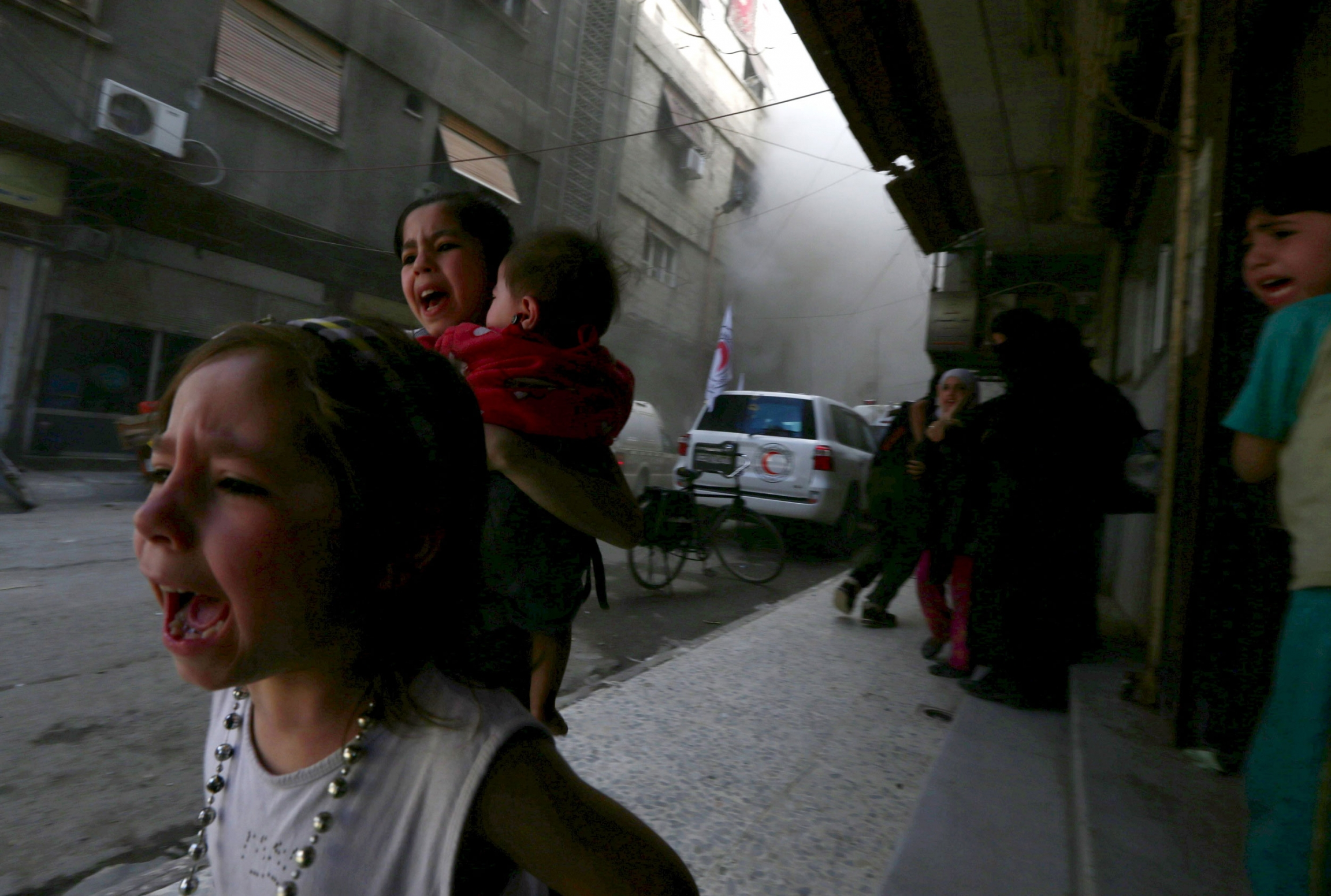 Ghazal, 4, (left) and Judy, 7, carrying 8-month-old Suhair, run away after the shelling of a Red Crescent convoy in Damascus, Syria, May 6, 2015.