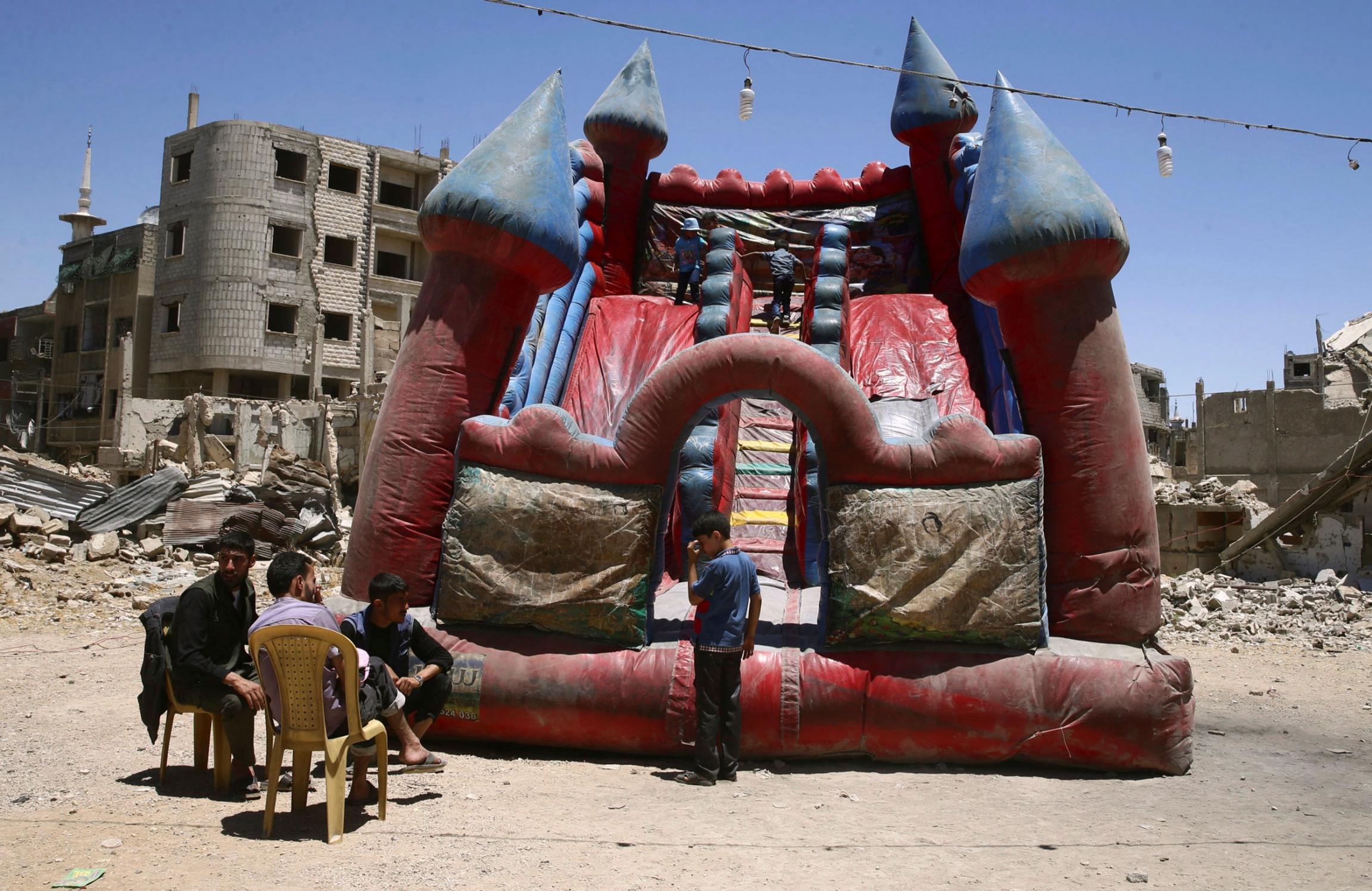 Children play inside an inflatable castle during Eid al-Fitr celebration in the Douma neighborhood of Damascus, Syria, June 26, 2017.