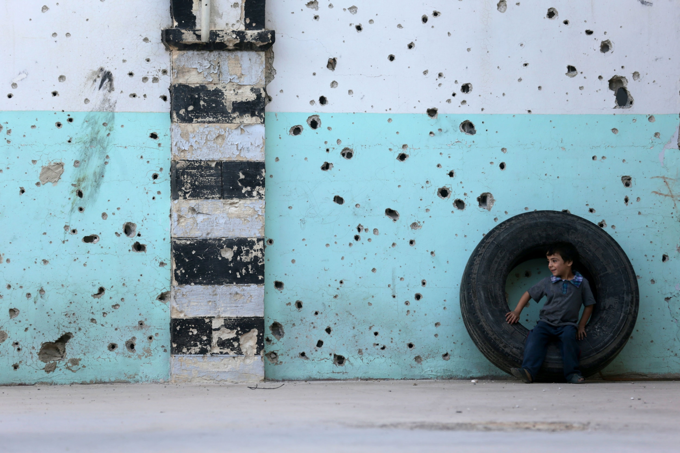 A young boy is shown sitting in a large tire against a blue wall riddled with bullet holes.