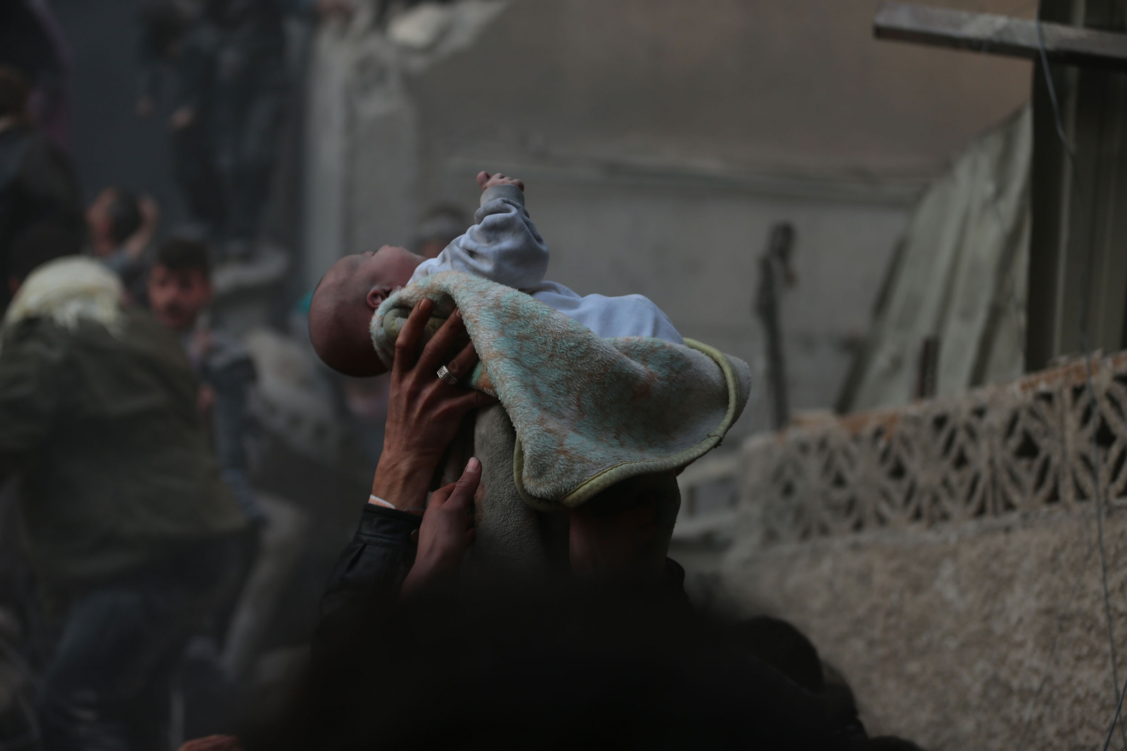 A small baby is shown wrapped in blanked and held above the heads people amid blackened walls of buildings.