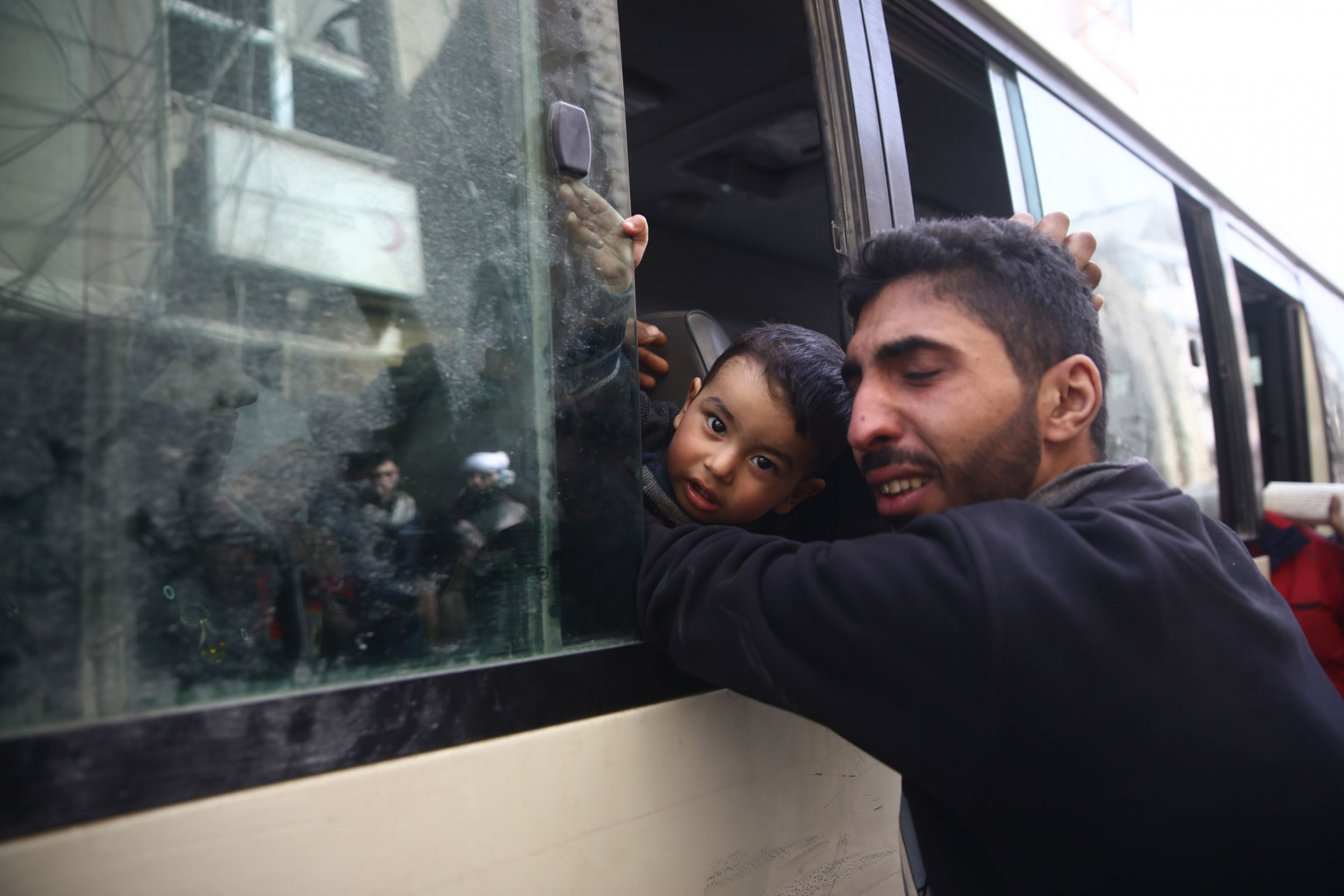 A man is shown reaching into a bus window and hugging his young son whom is staring at the camera.