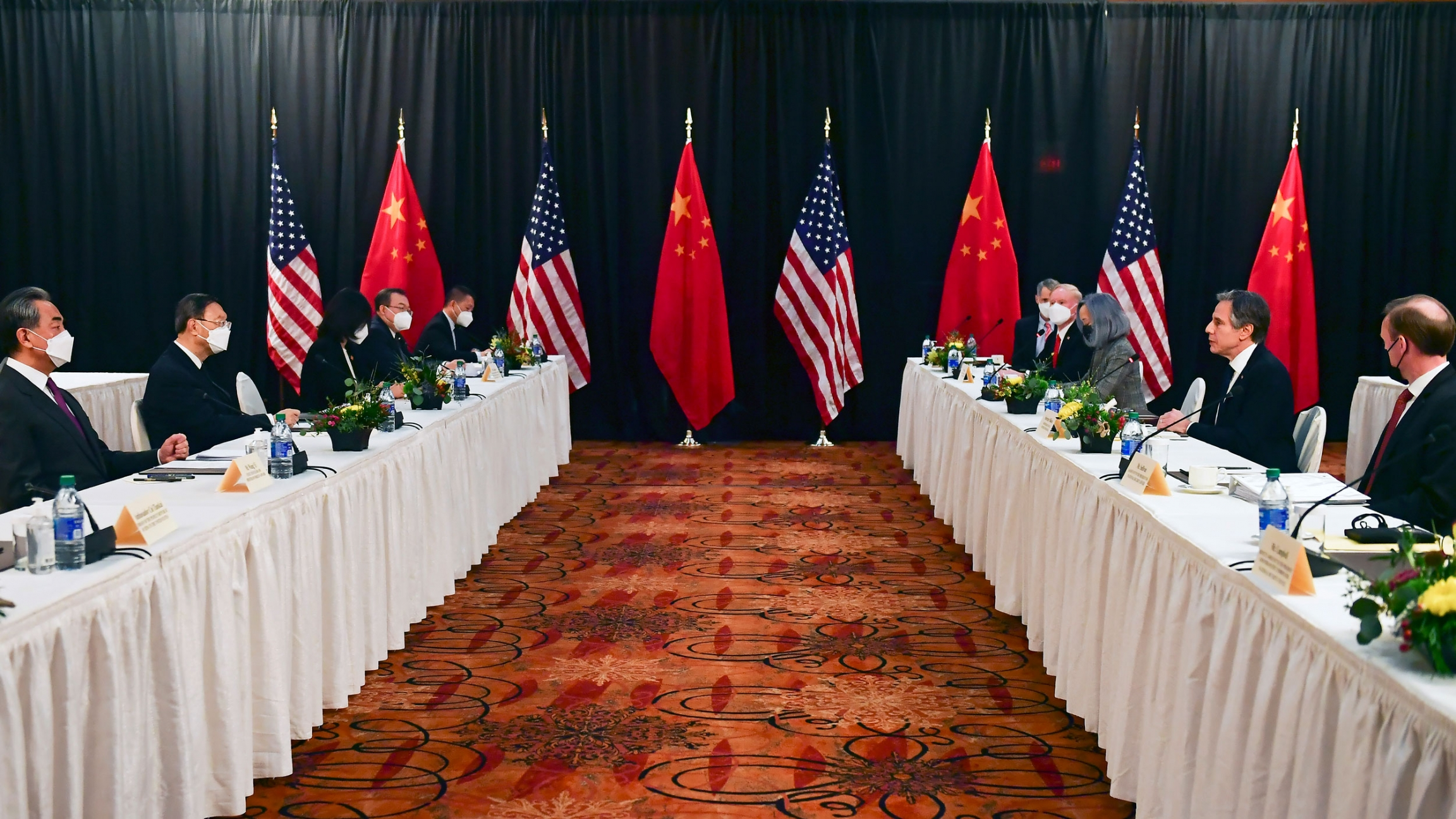 Two long rows of tables are shown with white table cloths and officials on either side with US and Chinese flags in the distance.