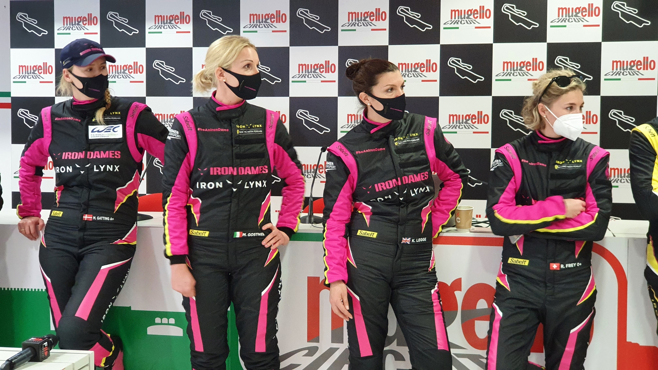 Four women wear black and pink race tracksuits.