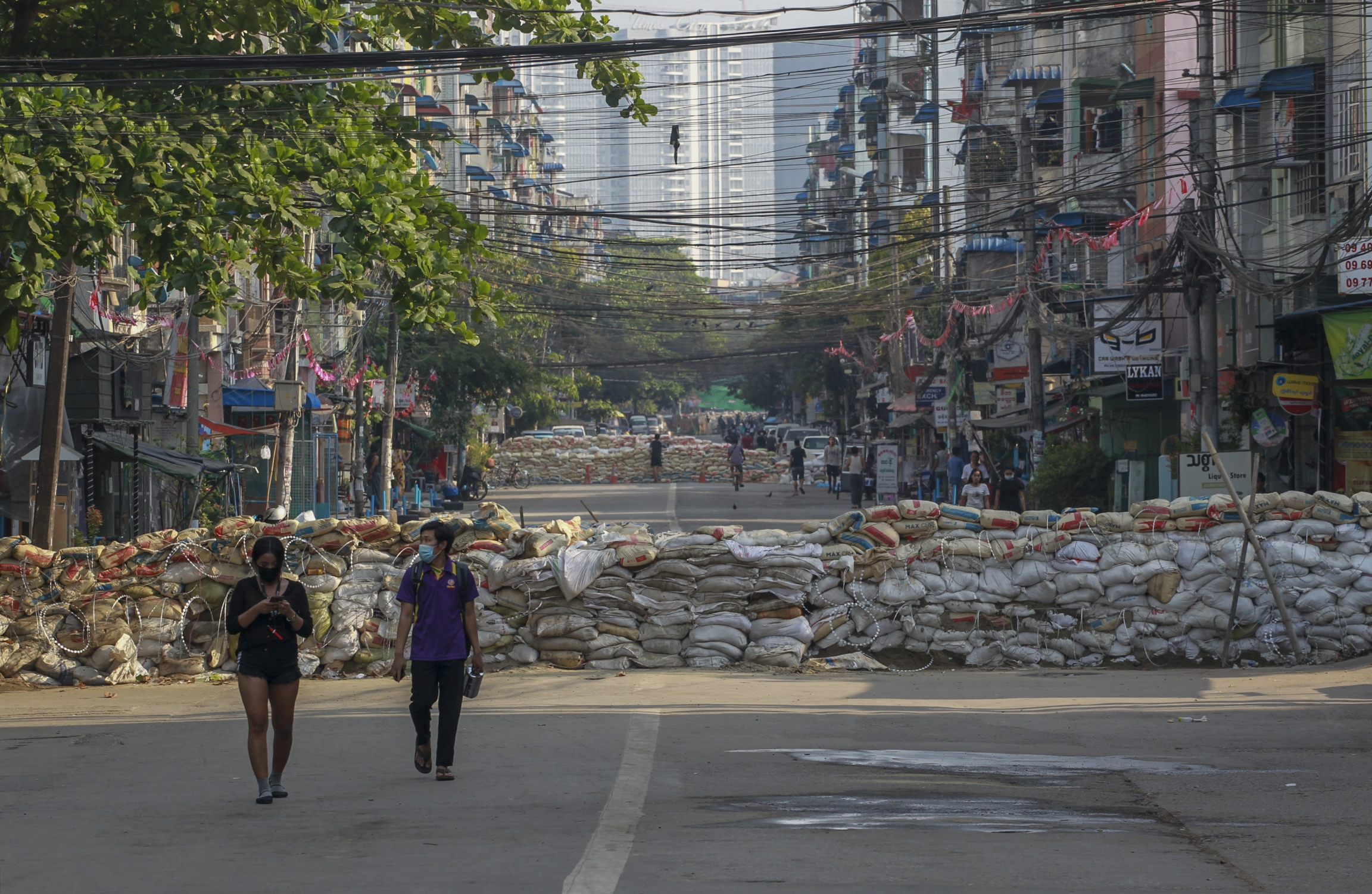 People walk along a deserted road blocked with improvised barricades build by anti-coup protesters to secure a neighborhood in Yangon, Myanmar, March 18, 2021.