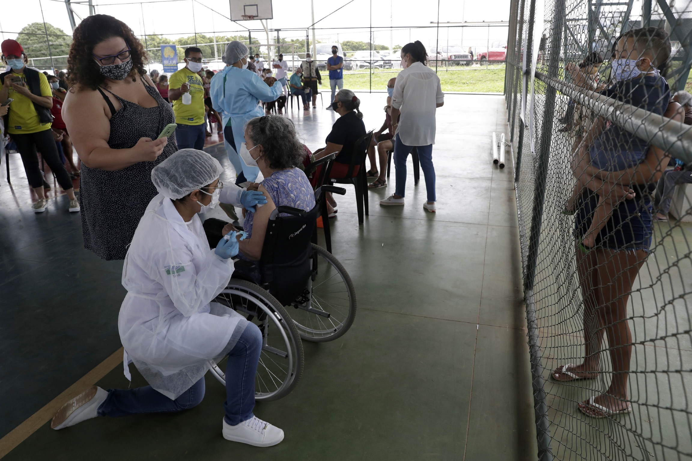 A health worker inoculates a woman at a COVID-19 vaccination point for priority elderly persons in the Ceilandia neighborhood, on the outskirts of Brasilia, Brazil, March 22, 2021.