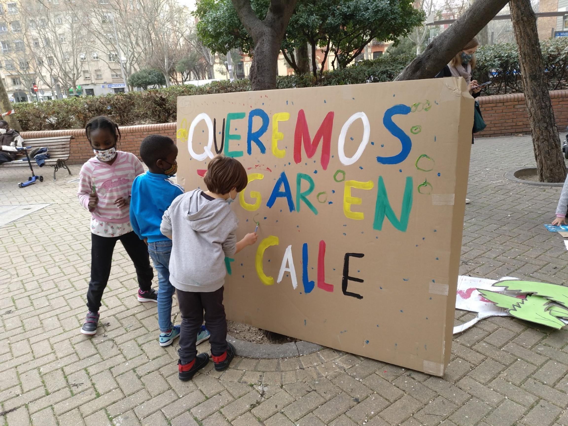 Children gather around an anti-car sign
