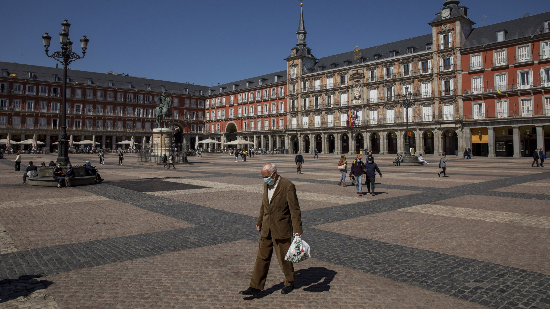 A man walks through a plaza during the day