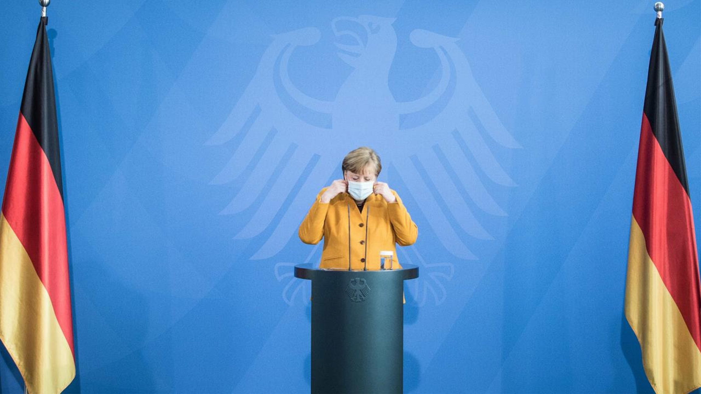 Merkel stands at a podium flanked by two German flags.