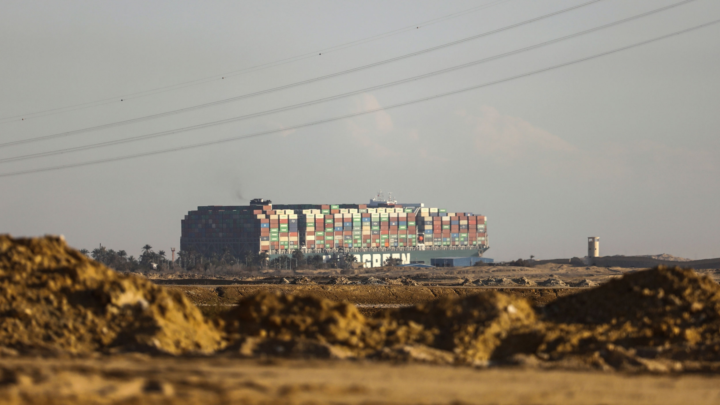A large cargo ship is show in the distance towering over the sandy landscape with hundreds of containers stacked on top.