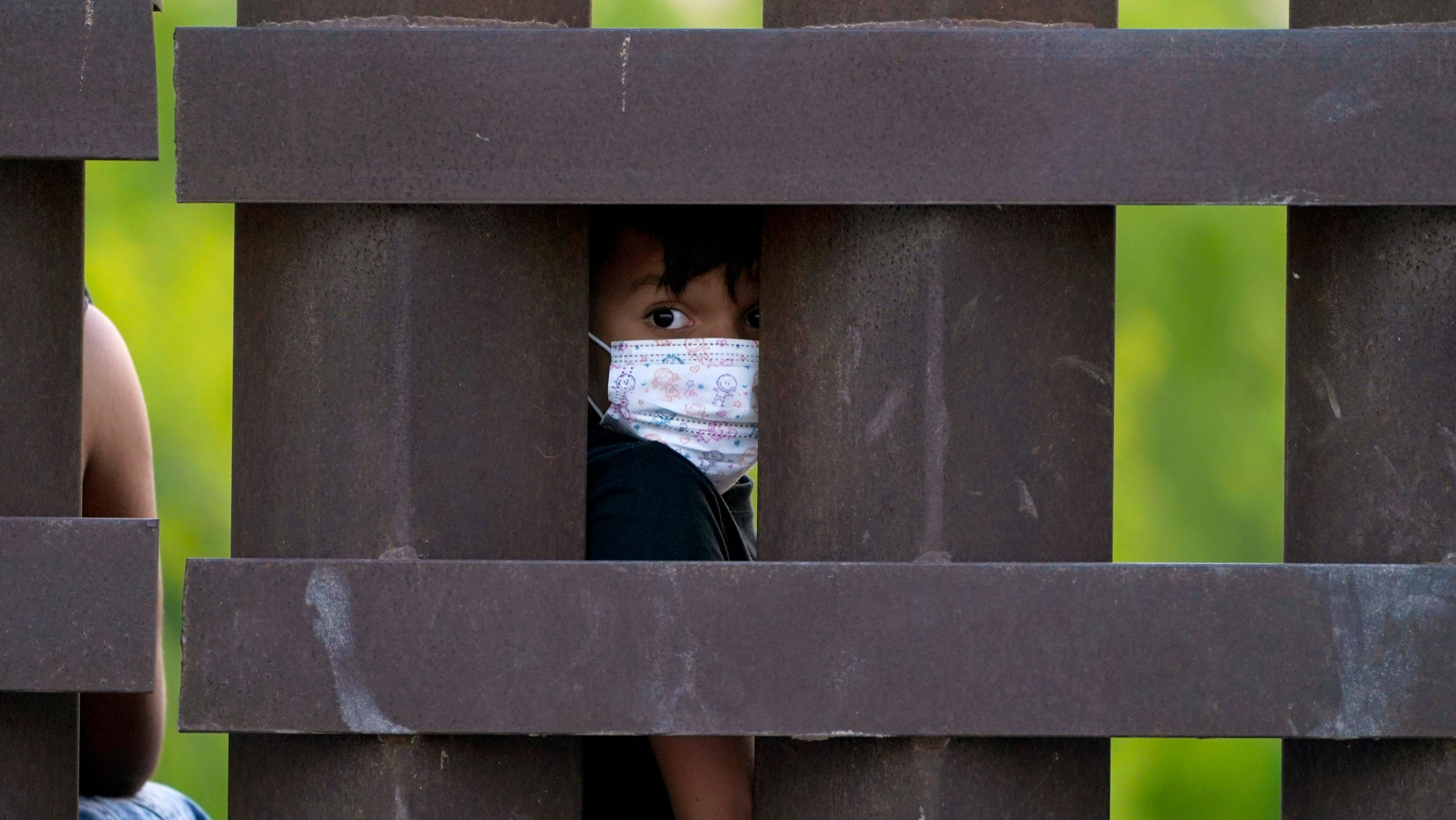 A small child is shown wearing a protective face mask and looking through the large medal polls of the US-Mexico border fence.
