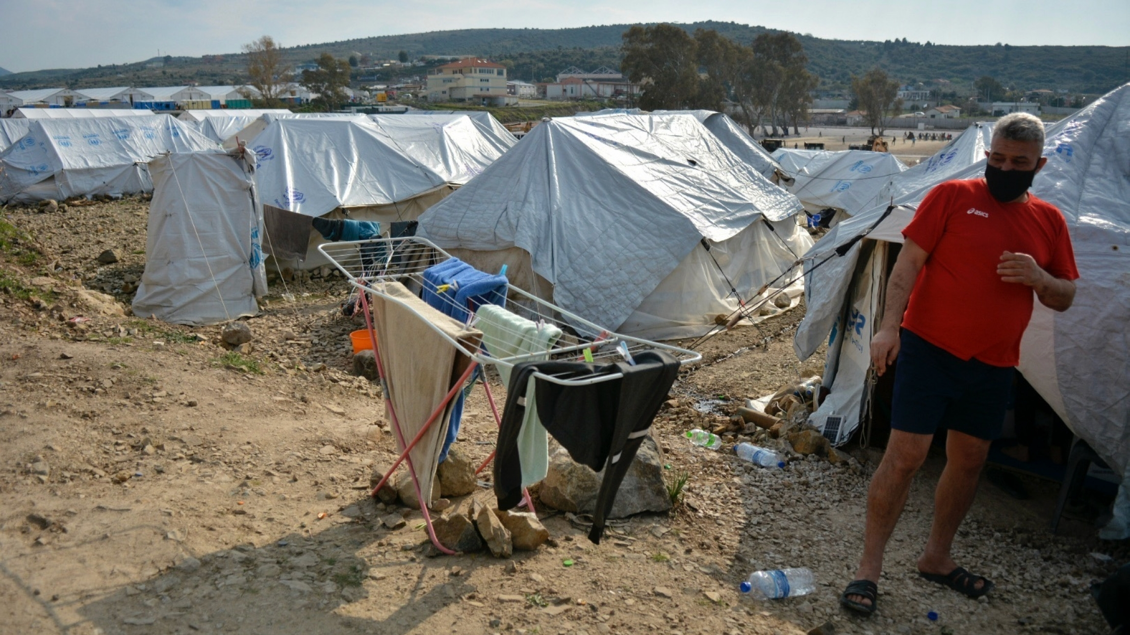 A migrant stands outside his tent at Karatepe refugee camp, on the northeastern Aegean island of Lesbos, Greece, March 29, 2021. The European Union's home affairs commissioner is visiting asylum-seeker facilities on the eastern Greek islands of Samos and