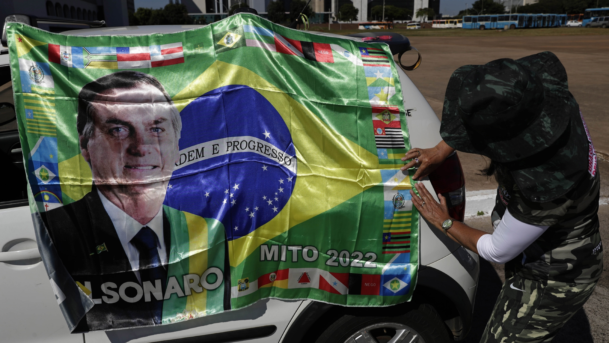 A supporter of Brazilian President Jair Bolsonaro places his image on a car.