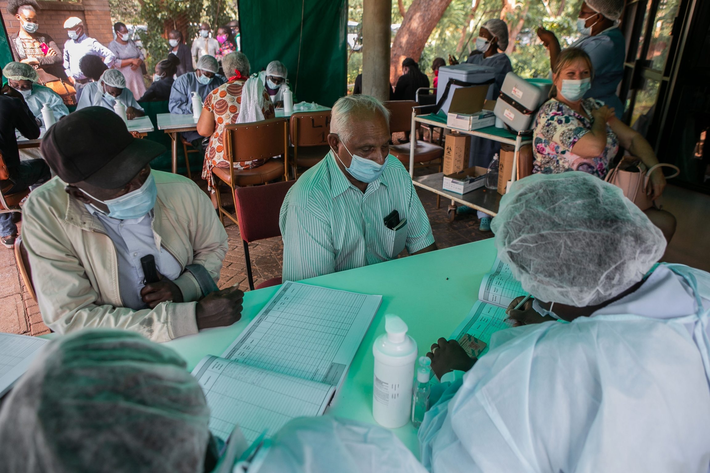 Citizens receive vaccinations with PPE-wearing health workers