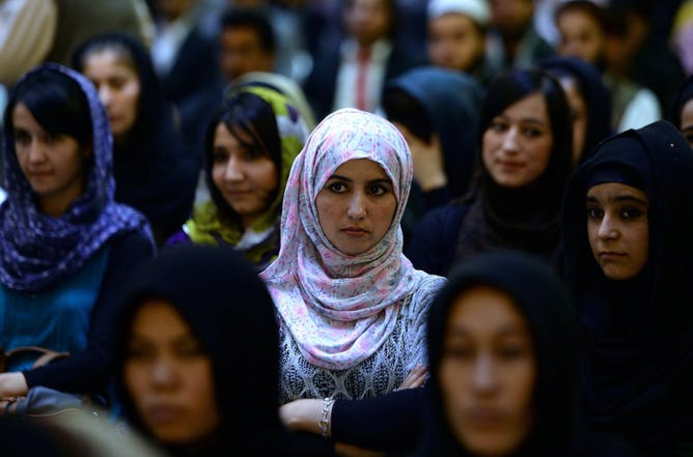 The camera focuses on a woman in an audience group of women.