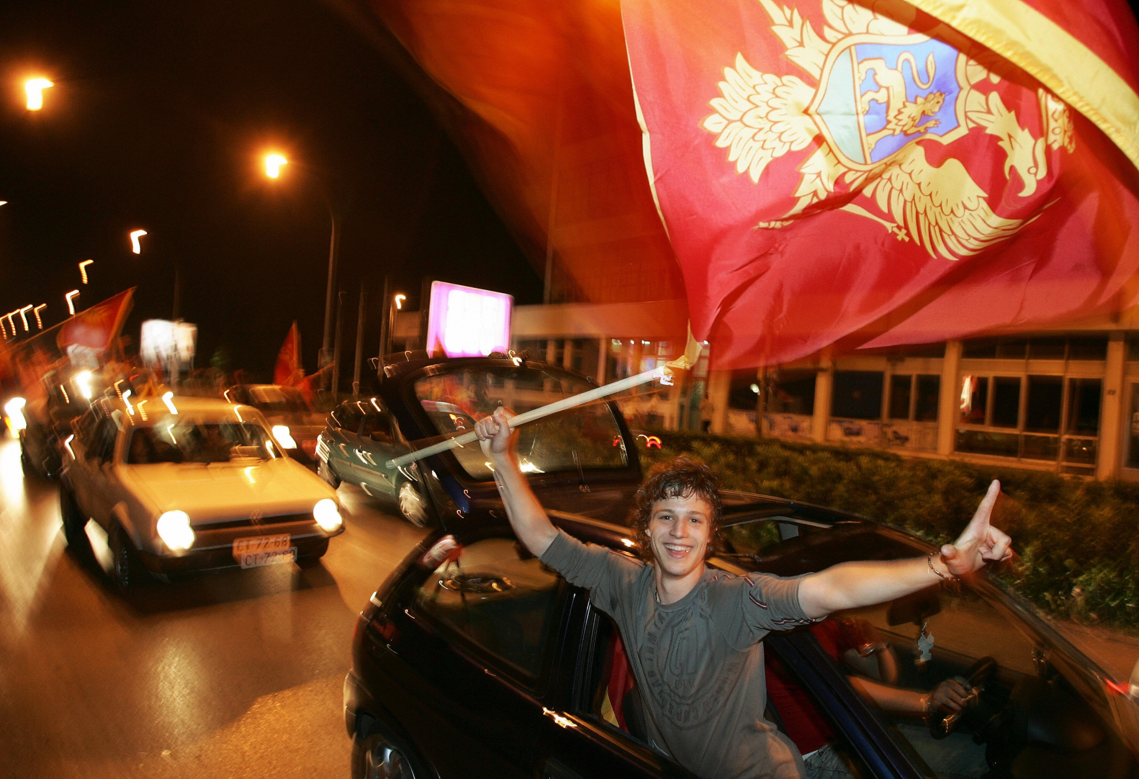 A man holds a flag and sticks his arm out of a car window, smiling and celebrating.