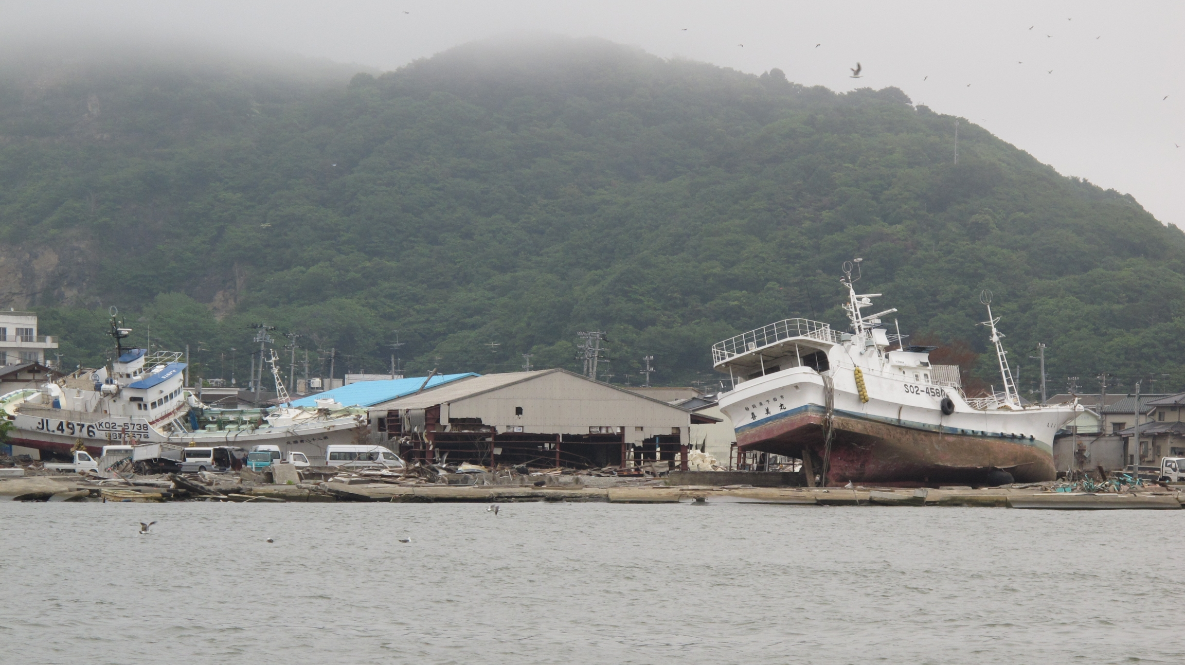 Several large boats are shown on their side and washed ashore following a tsunami as shown from across a body of water.