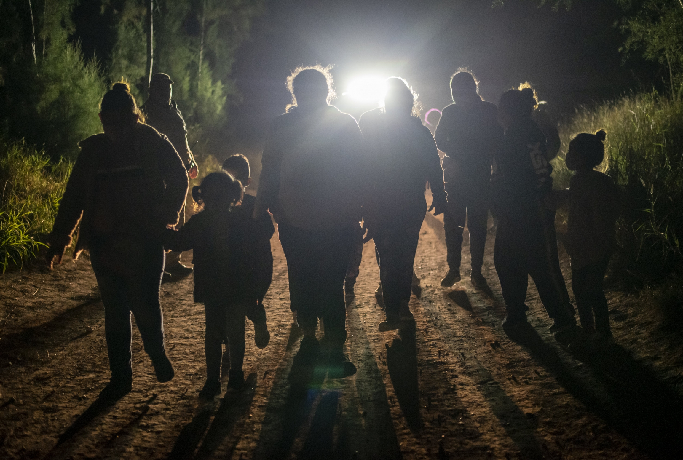 A group of noncitizens crossing the border at night, silhouetted against a light