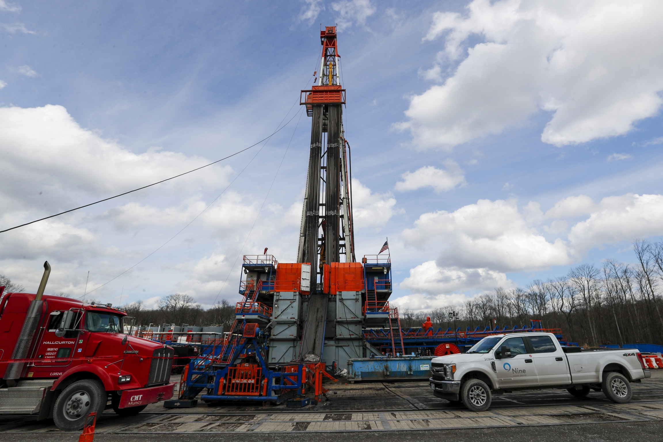 Red and white trucks flank a tall drilling well pictured against the sky