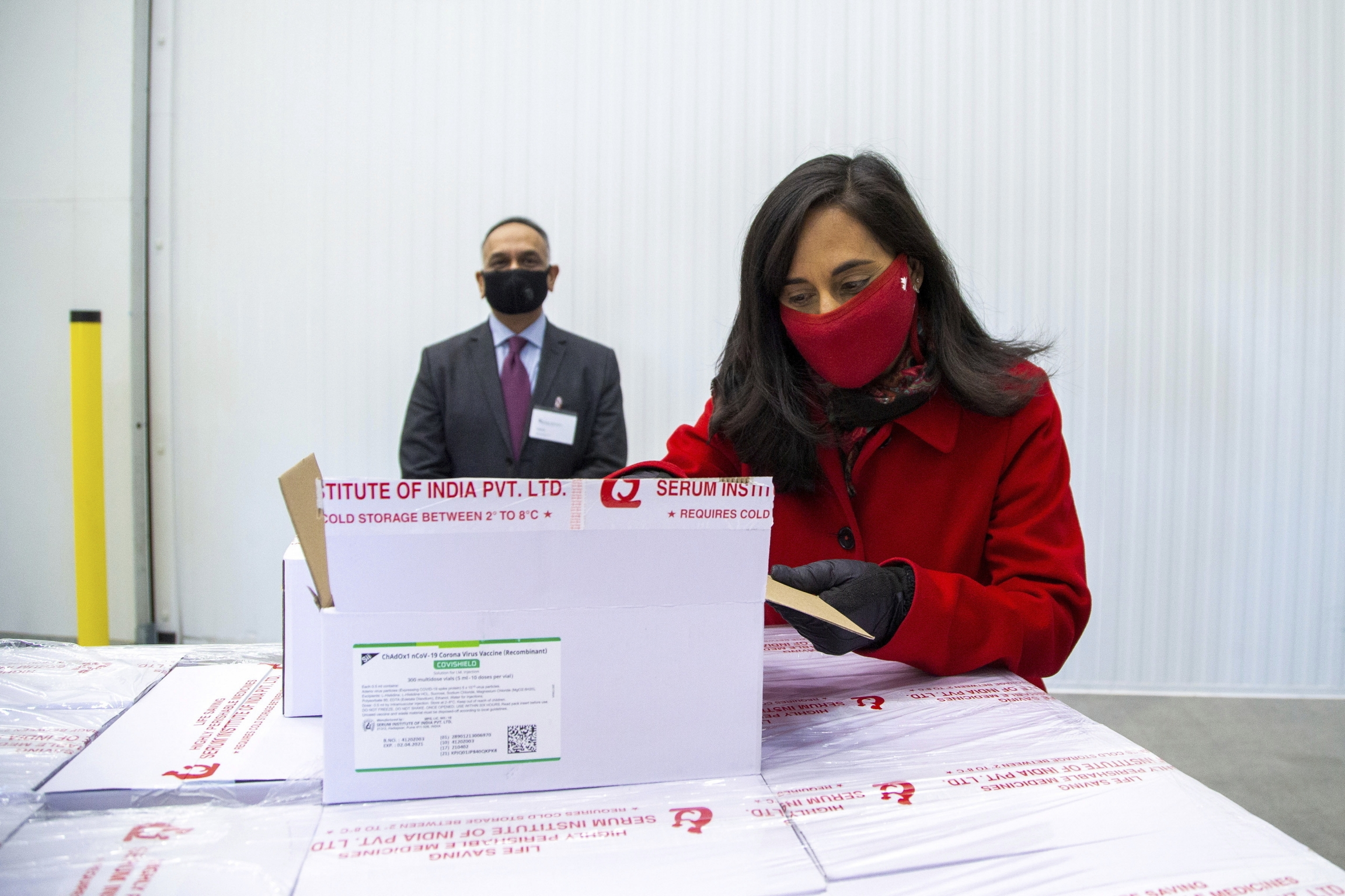 Anita Anand, Canada's Minister of Public Services and Procurement opens a box with some of the AstraZeneca COVID-19 vaccine doses that Canada has secured through a deal with the Serum Institute of India in partnership with Verity Pharma at a facility in M