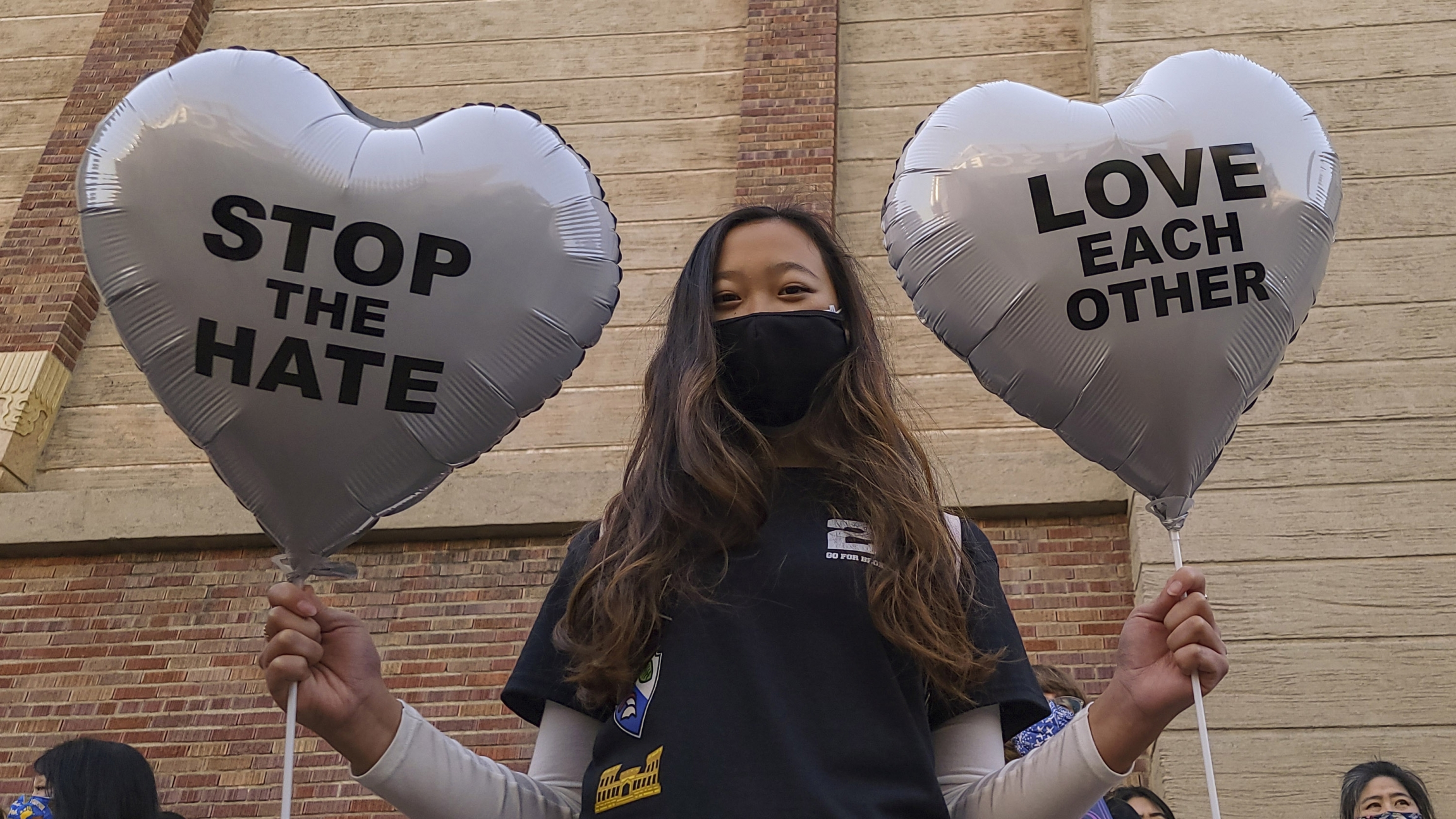 A young person holds up two balloons in heart-shapes that read Stop the Hate and Love Each Other